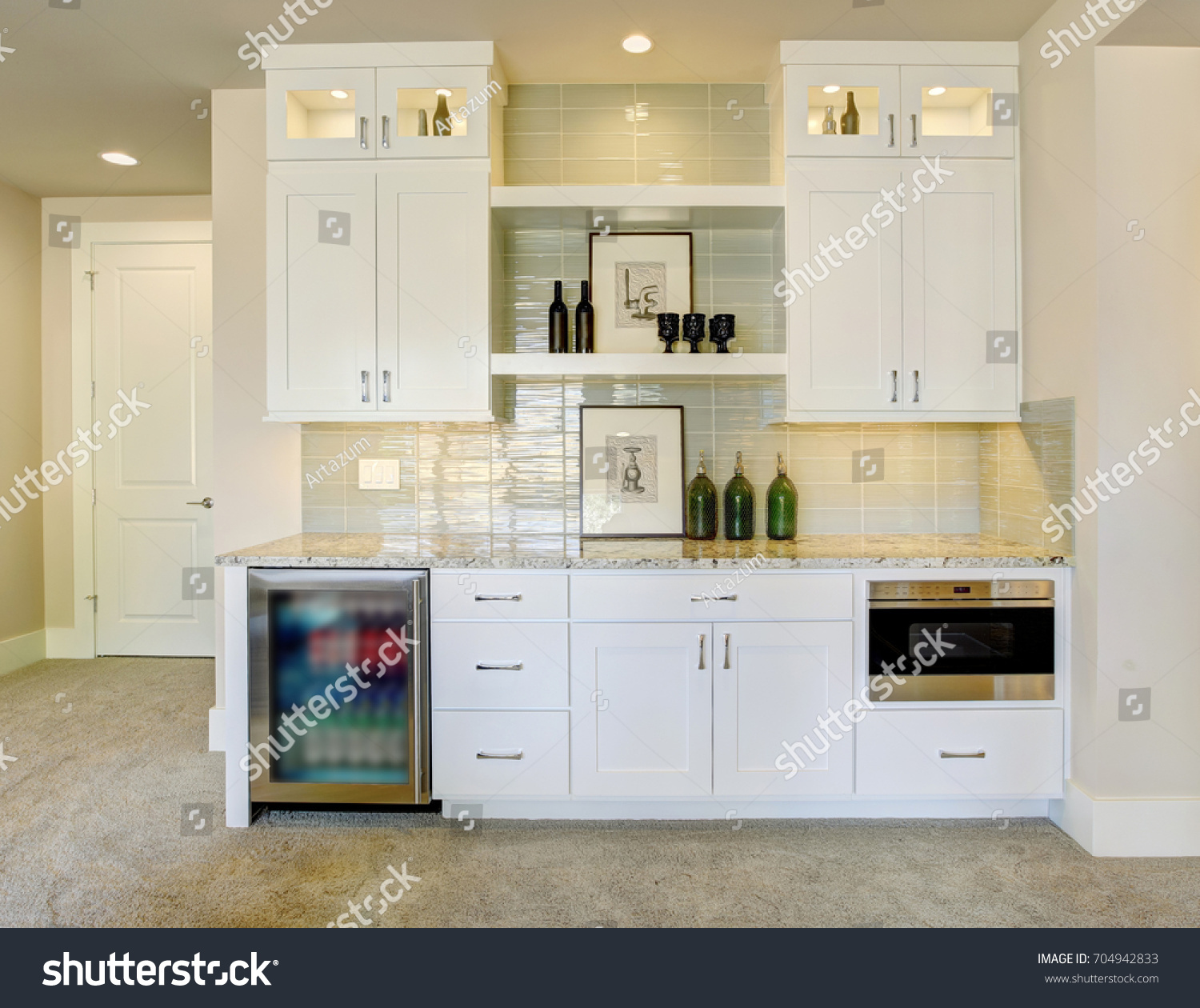 Wet Bar With White Cabinets Fitted With A Glass Door Beverage Fridge,  Granite Counter Top