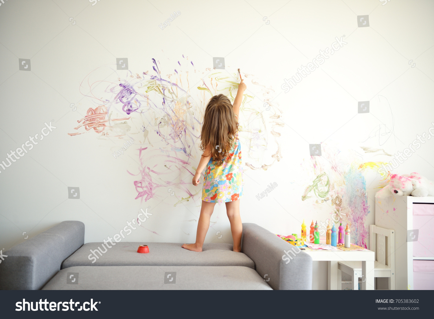 Curly cute little toddler girl painting with paints color and brush on the wall. Works of child #705383602