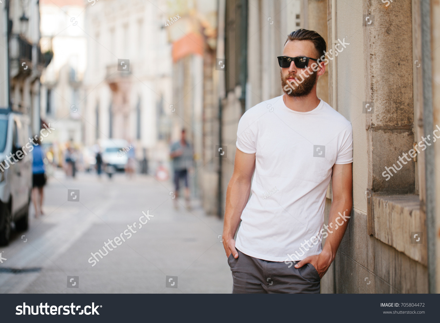 Hipster handsome male model with beard wearing white blank t-shirt with space for your logo or design in casual urban style #705804472