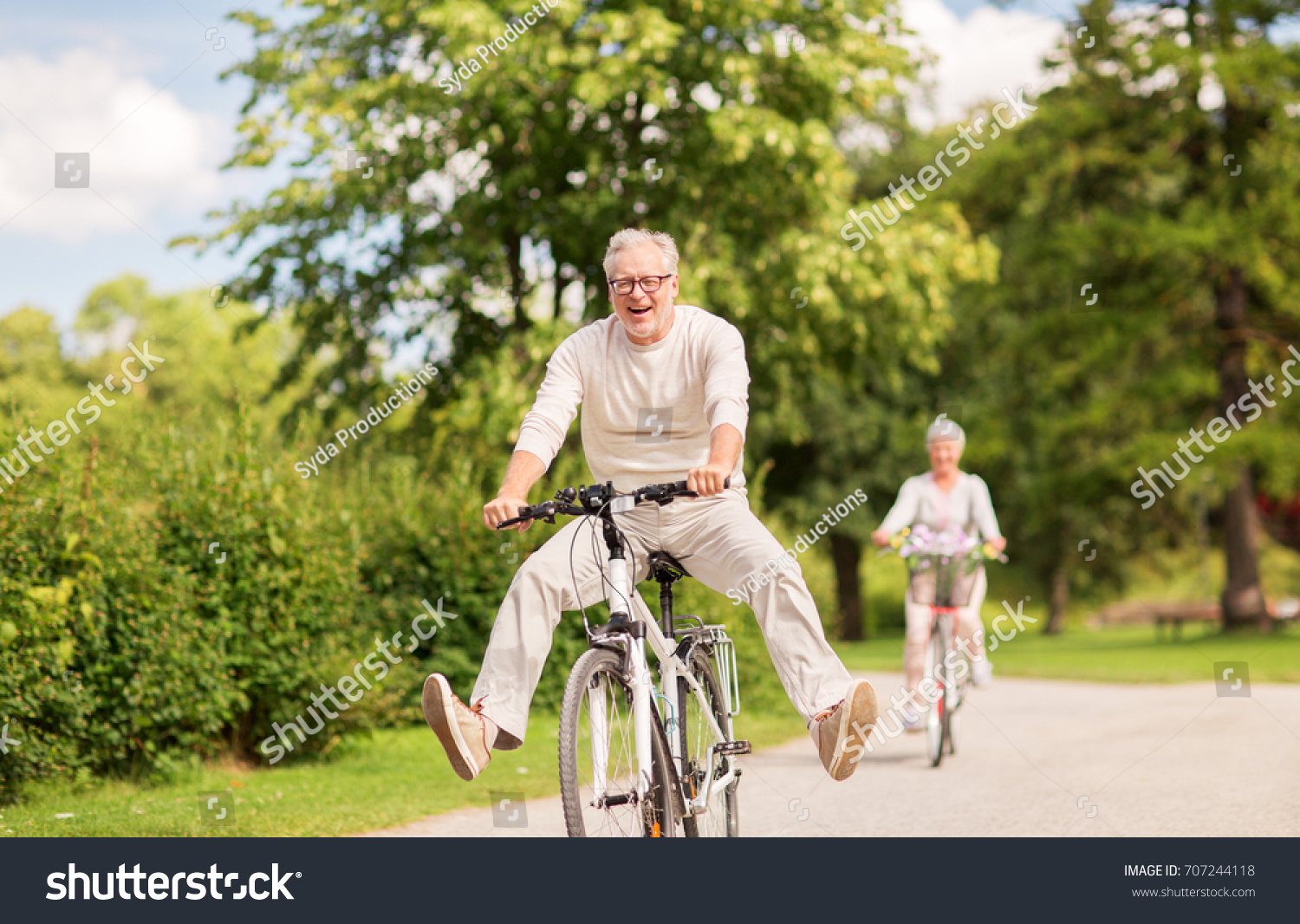 active old age, people and lifestyle concept - happy senior couple riding bicycles at summer park #707244118
