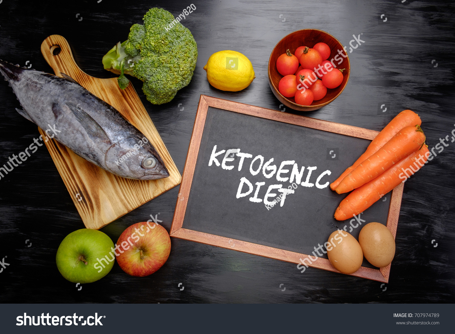 Ketogenic Diet (or Keto Diet) on chalkboard, health conceptual. Healthy fresh low carbohydrates food; egg, fish, lemon, tomatoes, apple, carrot and broccoli. #707974789
