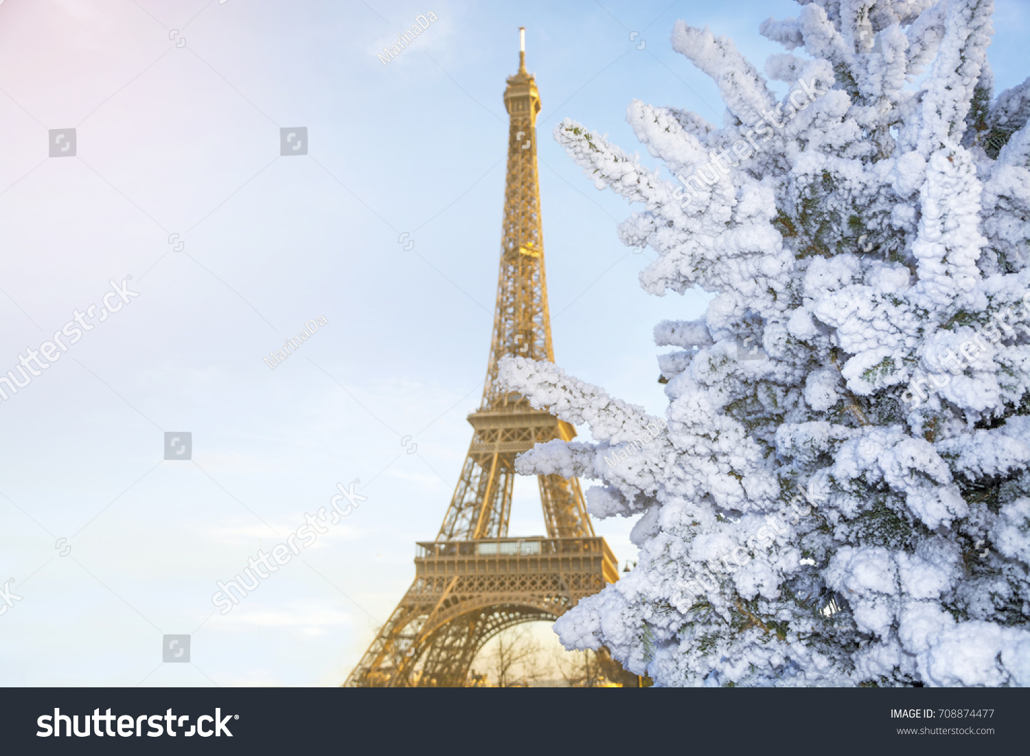 eiffel tower is the main attraction of paris on the background of decorated christmas trees in
