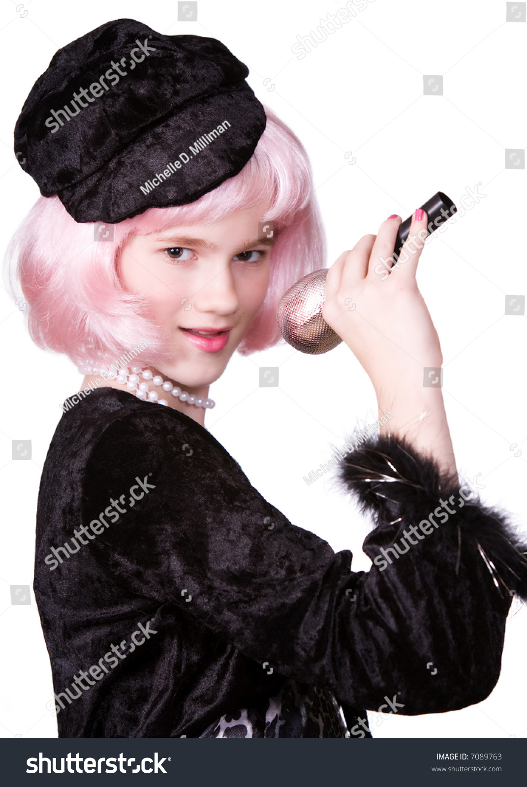 black preteen Beautiful preteen with pink hair and dressed in black holds a microphone by  her mouth.