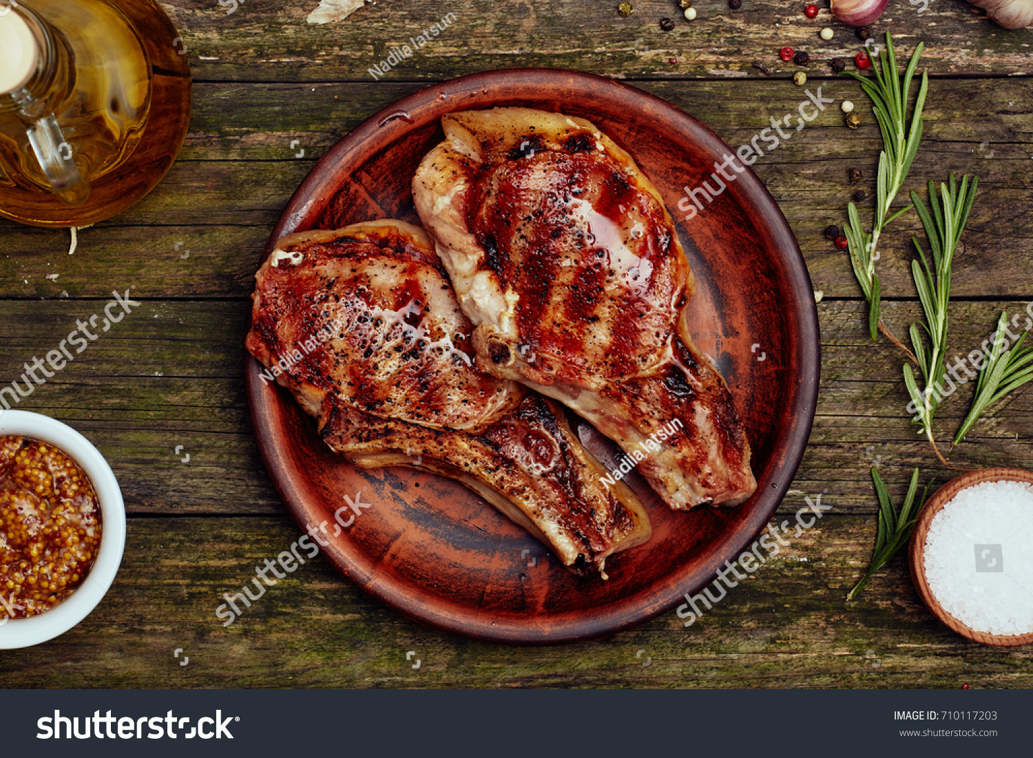 Grilled pork rib chop steak in a clay plate  with oil, mustard, salt and rosemary on an old rustic wooden table. Top view, flat lay.
