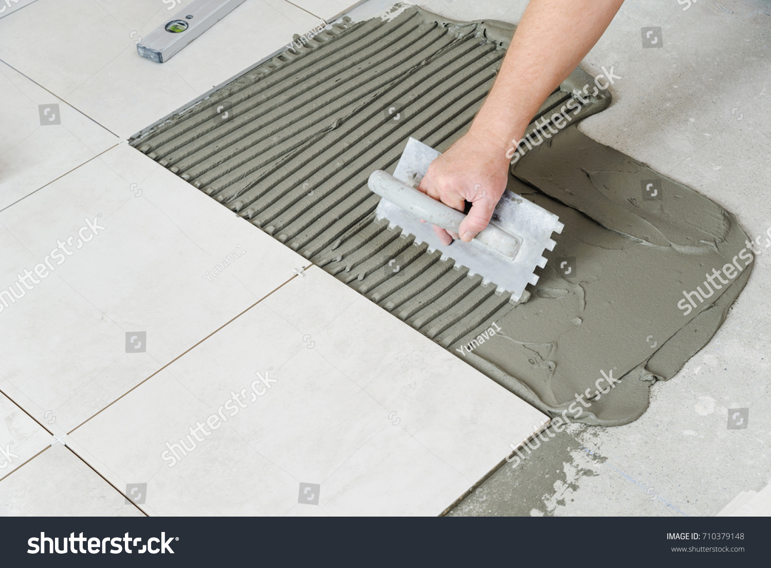 Workers hand putting tiles adhesive wall stock photo 710379148 the workers hand is putting tiles adhesive to the wall with the notched trowel dailygadgetfo Gallery