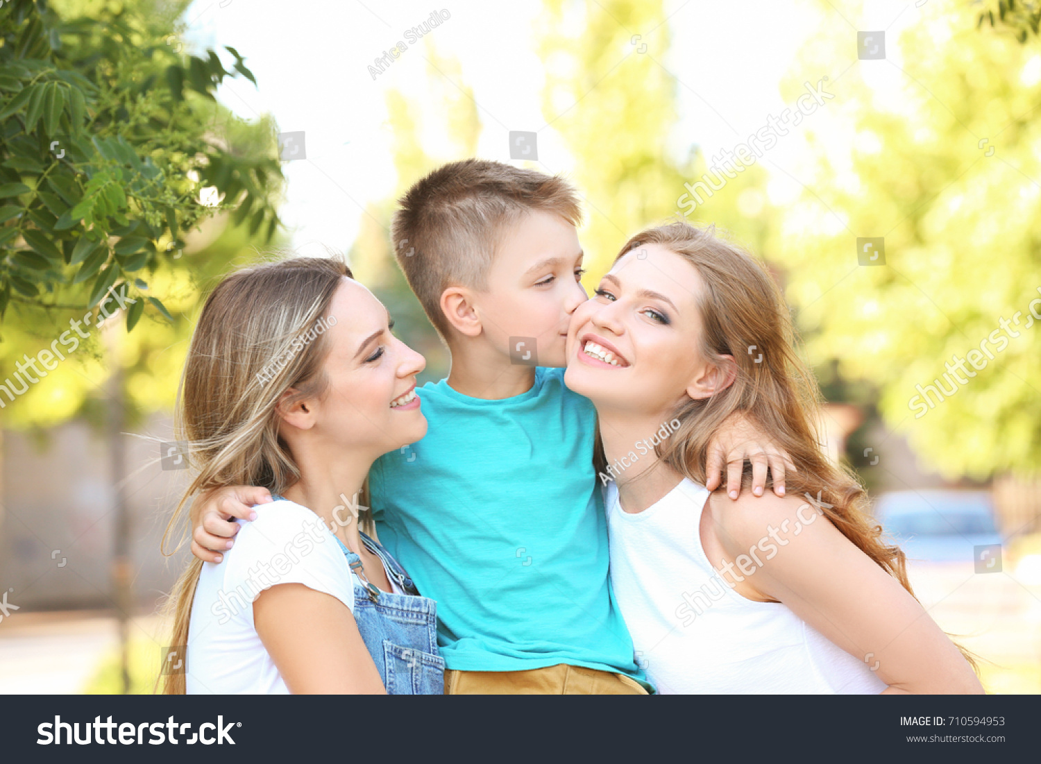 Lesbian mothers and foster son having fun outdoors