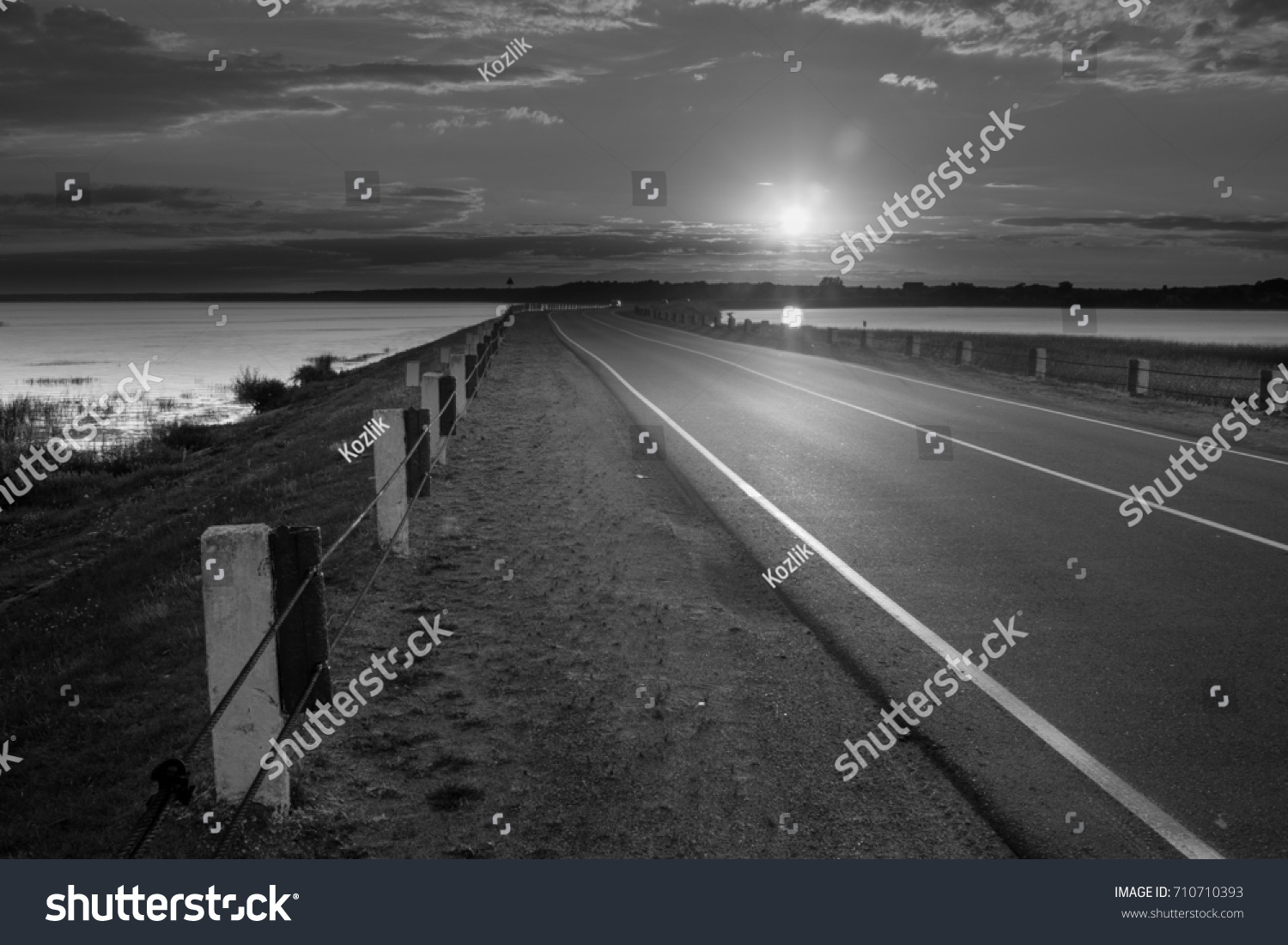 Road with beautiful scenery lake and sky black and white photo