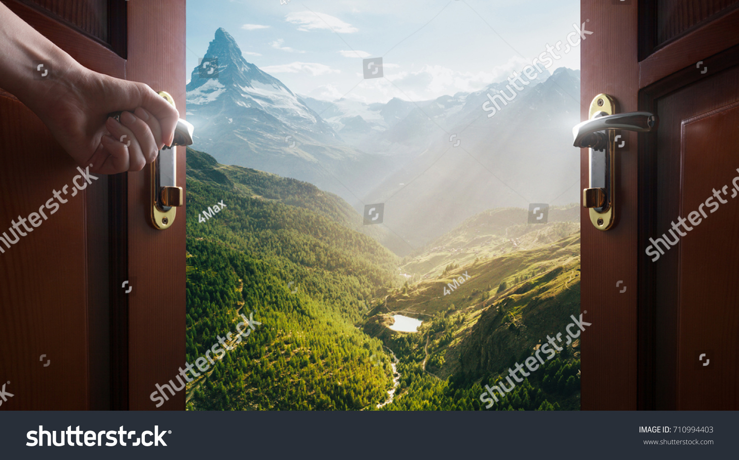 hand opens empty room door to nature and mountains