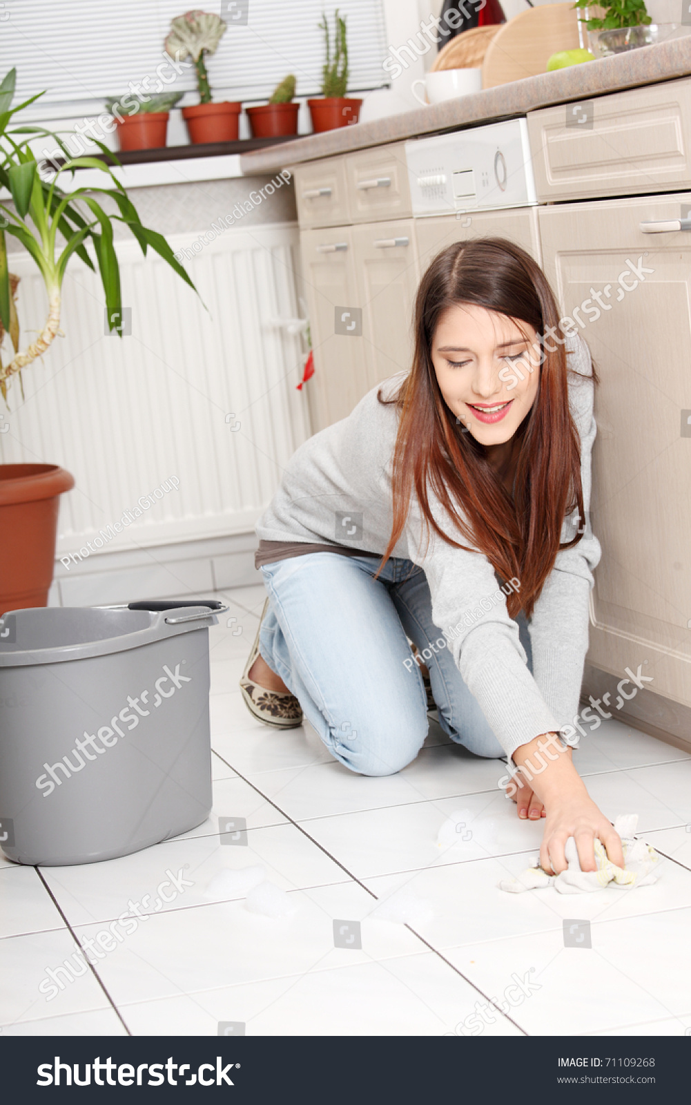 Young Happy Woman Cleaning Flor On Her Knees Stock Photo