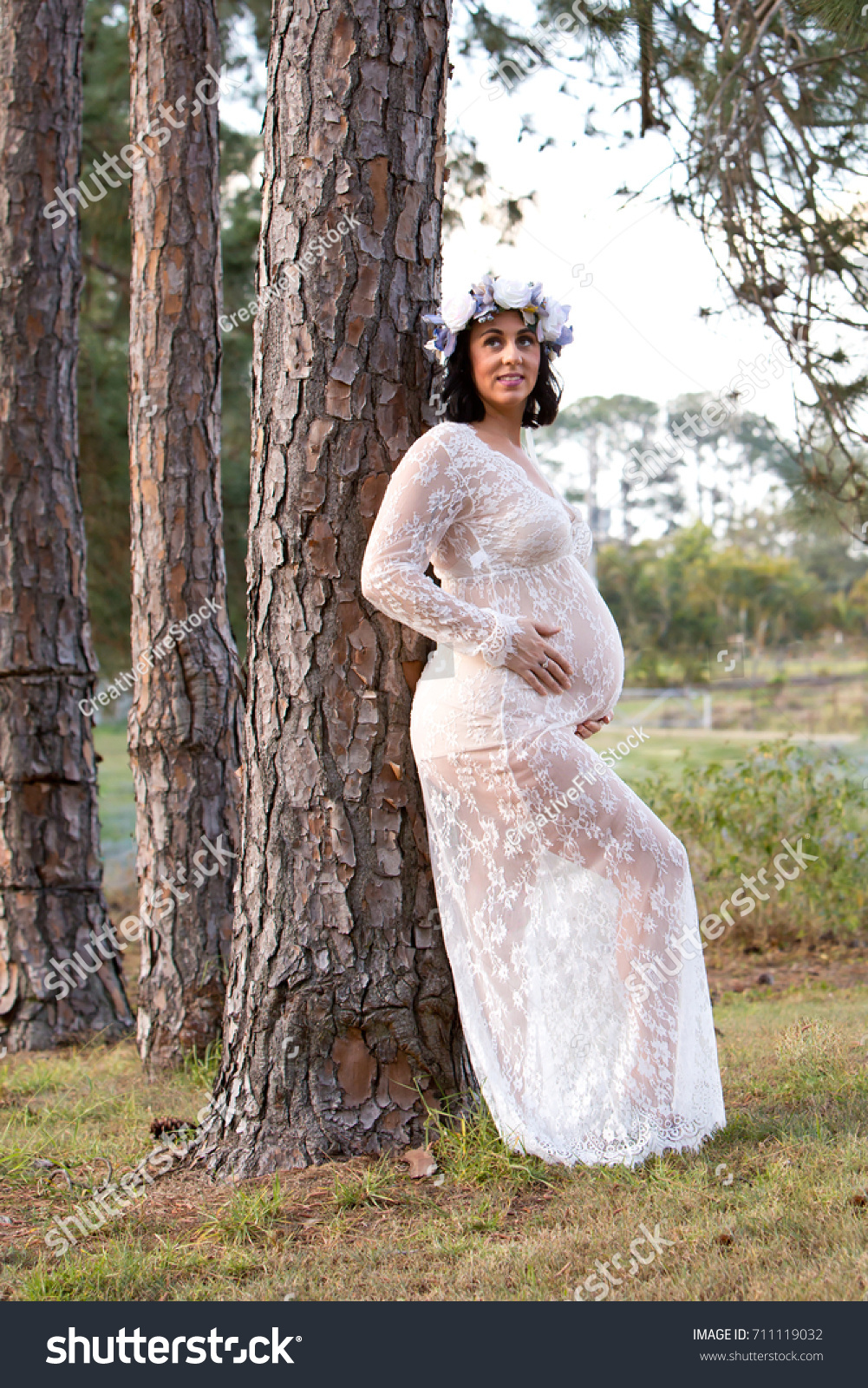 22894bb2f9ff3 Beautiful pregnant woman in sheer white lace maternity dress outdoors  leaning against large pine tree trunk