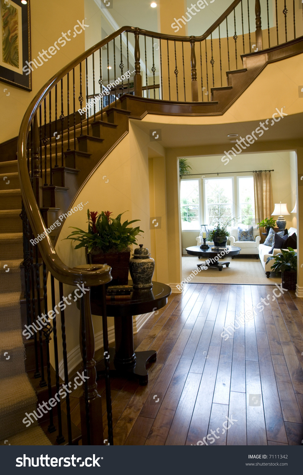 Attractive Mansion Hallway With Winding Staircase And Luxurious Decor.