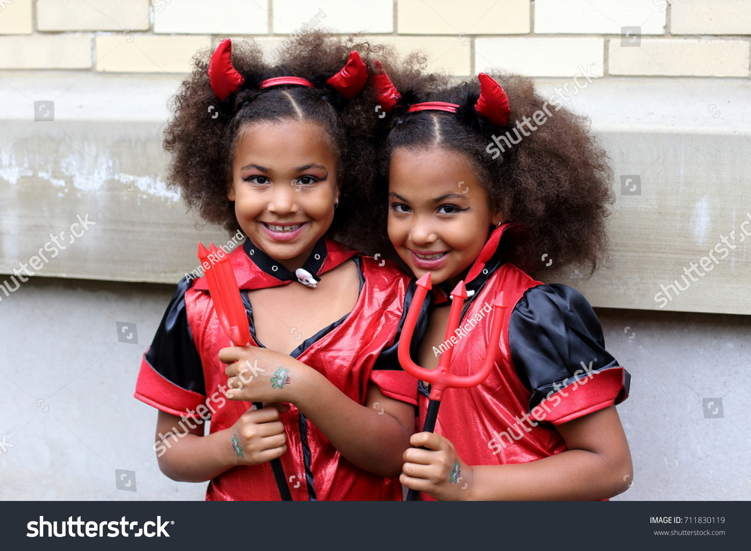 Identical african american girl twins disguised as devils to participate in the 2015 just for