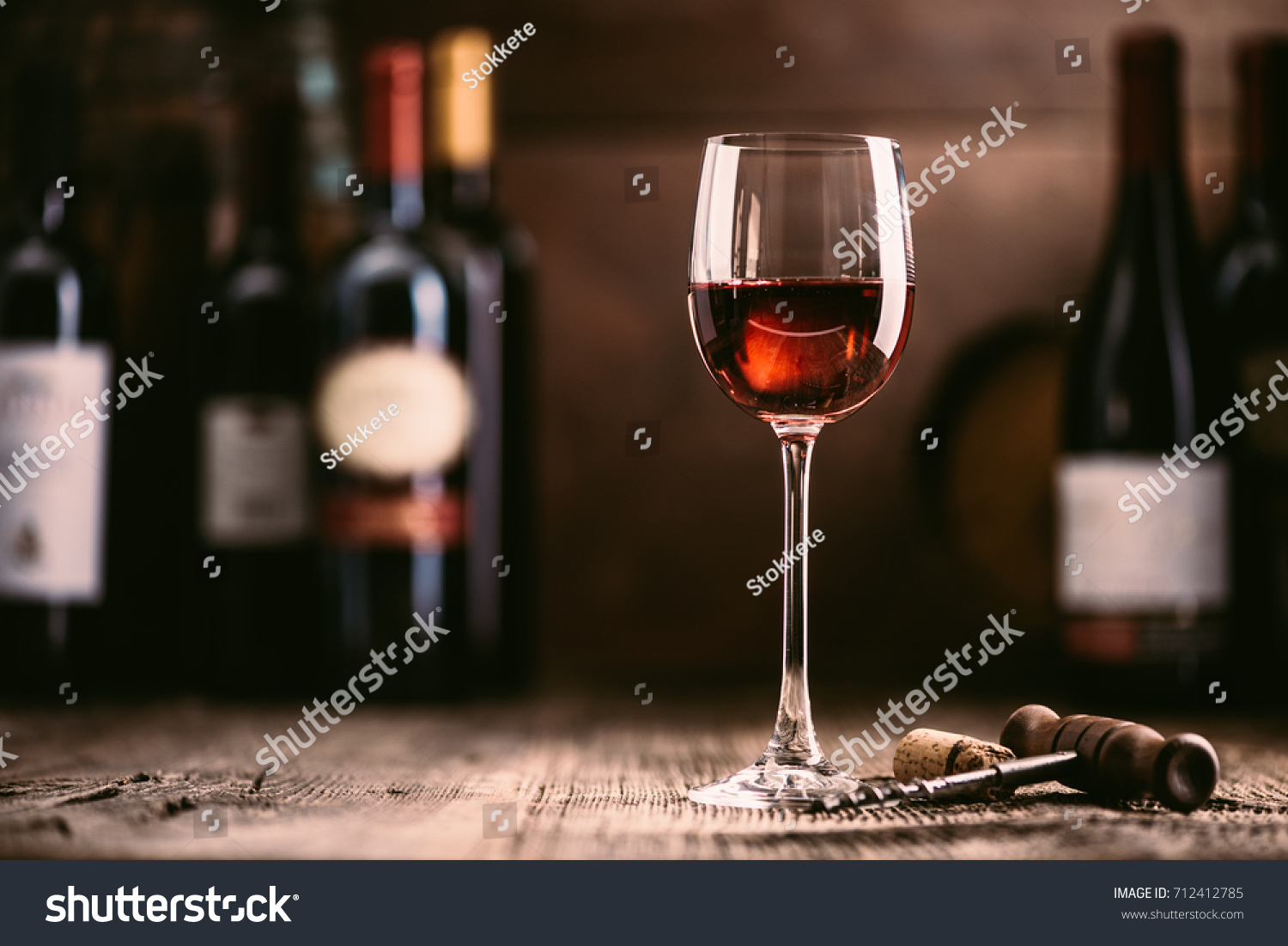 Wine tasting experience in the rustic cellar and wine bar: red wine glass and collection of excellent wines on the background #712412785