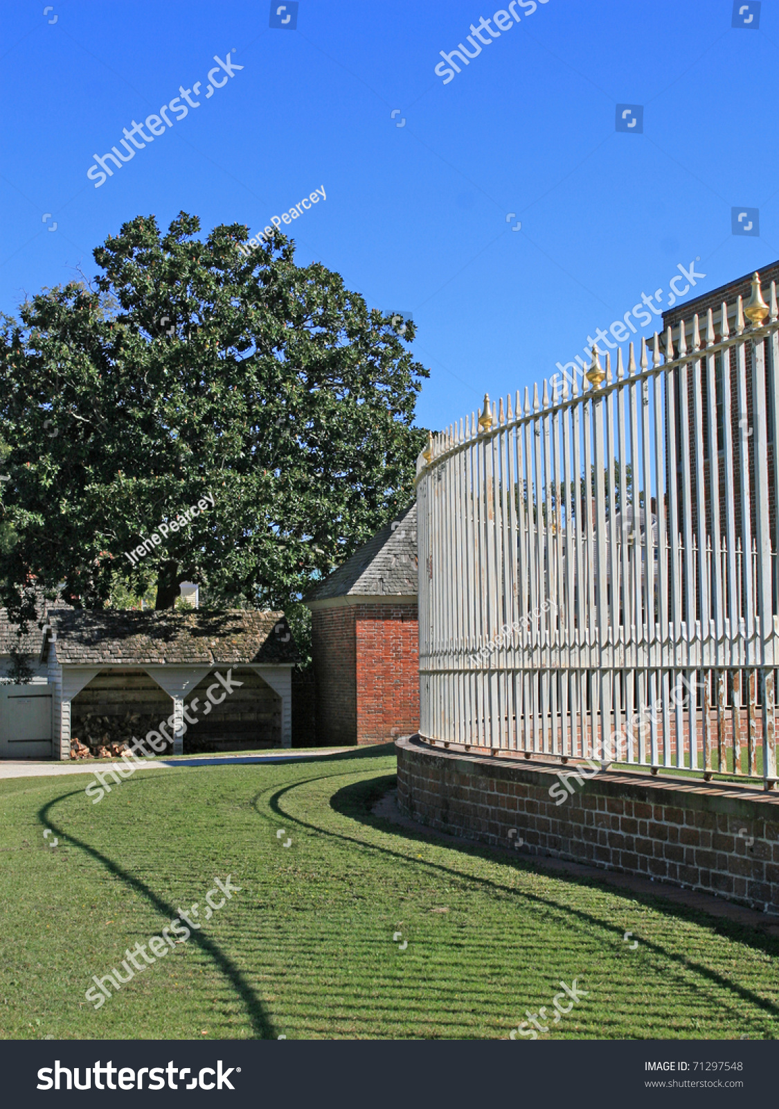 White wrought iron fence shadowed on green lawn stock