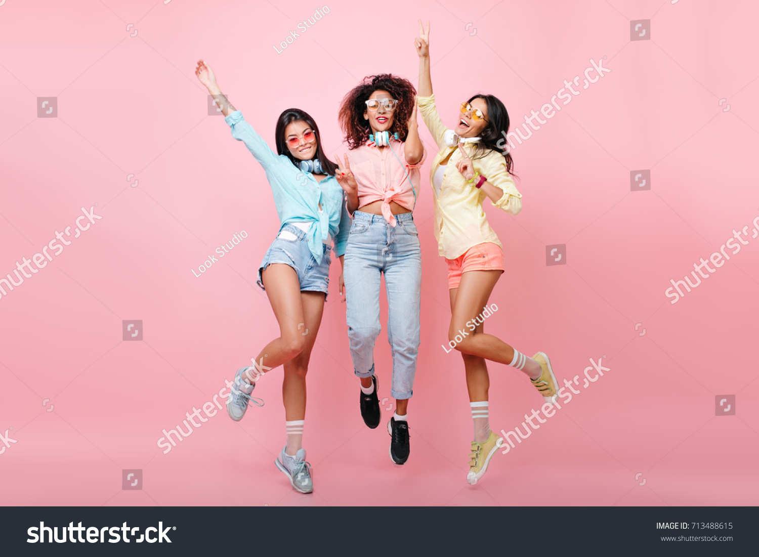 Curly african woman in jeans jumping while posing with international university friends. Tanned latin girl in yellow shirt dancing on pink background and having fun with other ladies. #713488615