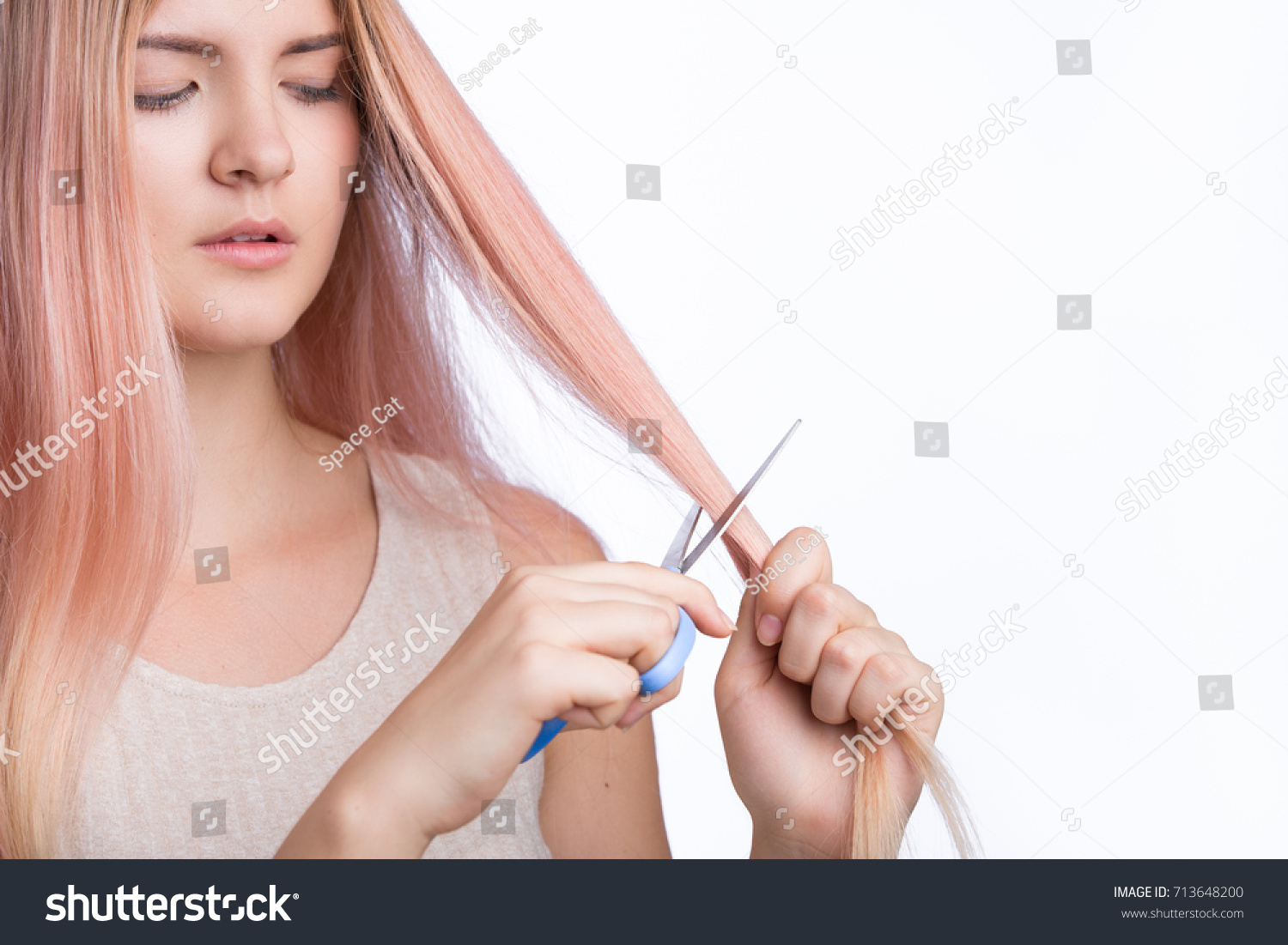 Young girl with golden pink hair cutting her hair with scissors isolated on white