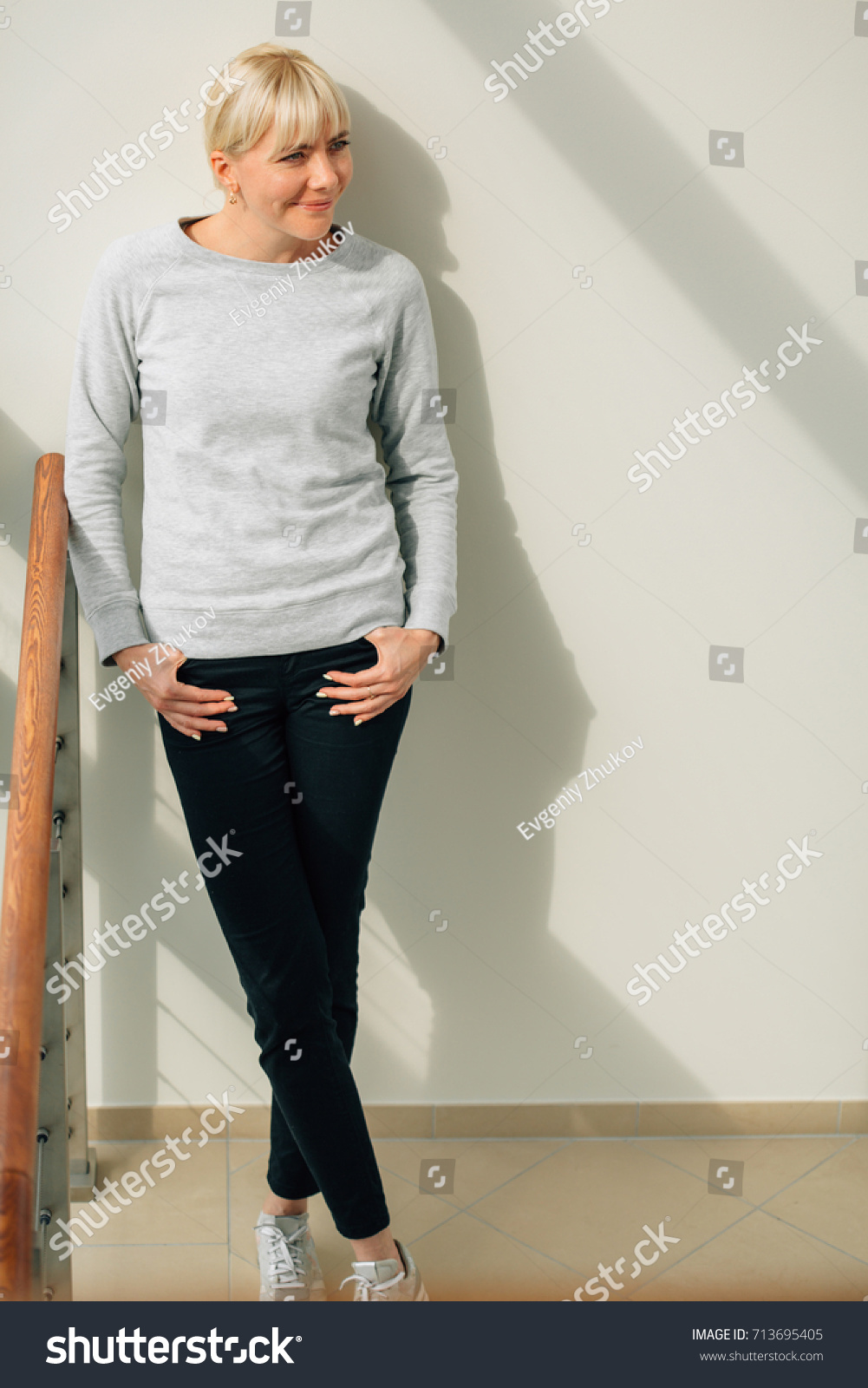 644d306049 Young stylish blonde woman in white sweater black pants and sneakers  standing near window. Cute