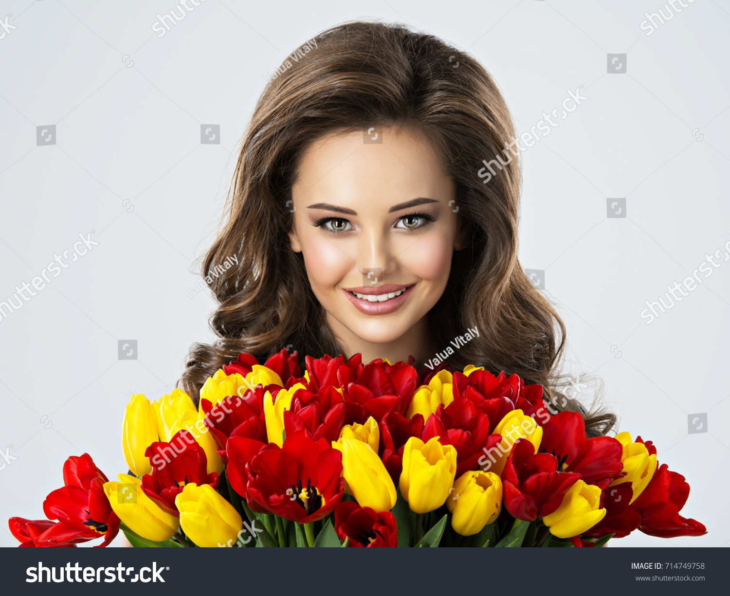 Portrait beautiful happy woman flowers hands stock photo 714749758 portrait of beautiful happy woman with flowers in hands young attractive young girl holds the dhlflorist Gallery