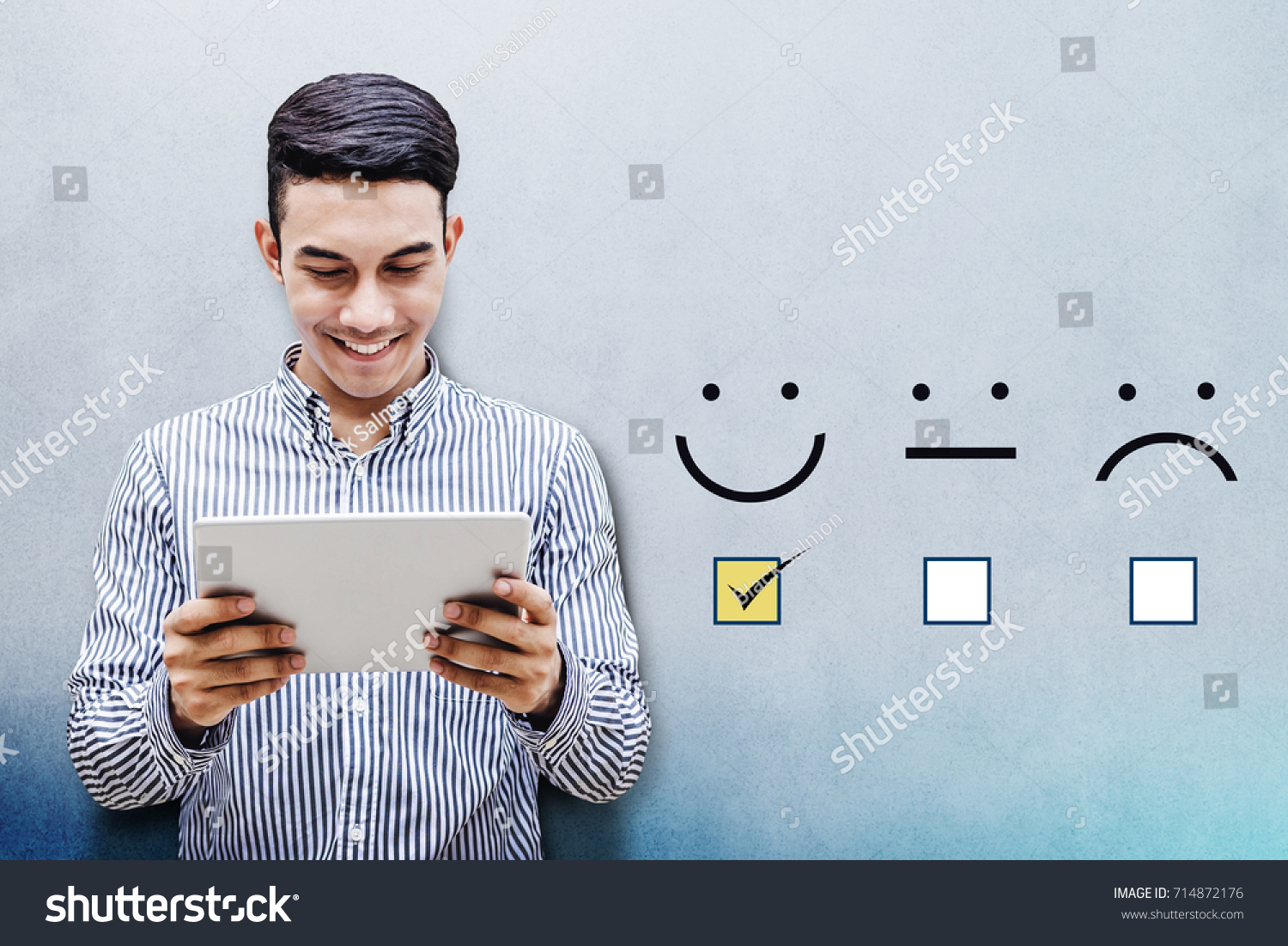 Customer Experience Concept, Happy Businessman holding digital Tablet with a checked box on Excellent Smiley Face Rating for a Satisfaction Survey #714872176