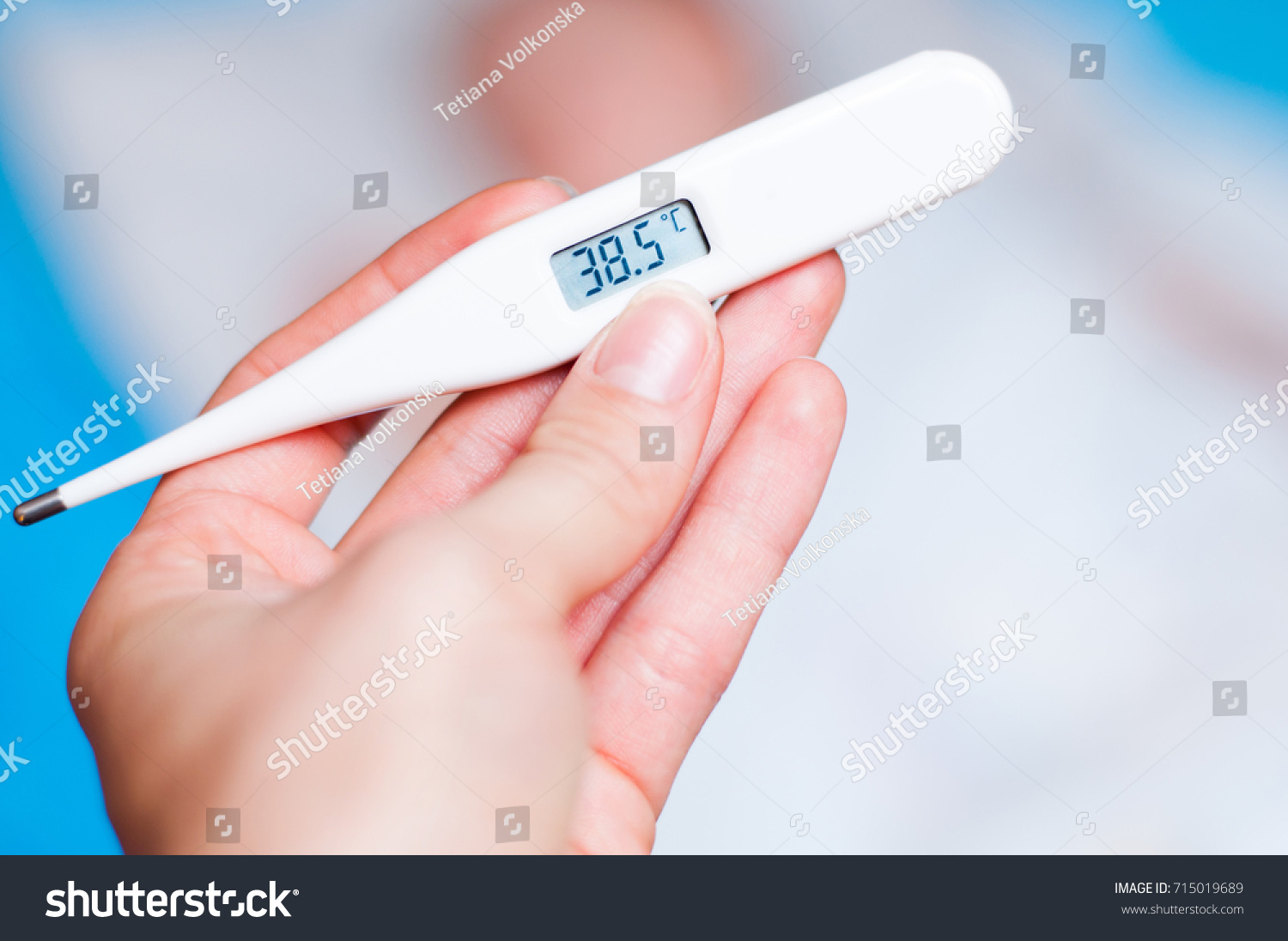The Hand Holds A Thermometer With 385 Degrees Celsius On Background Of Child Sleeping