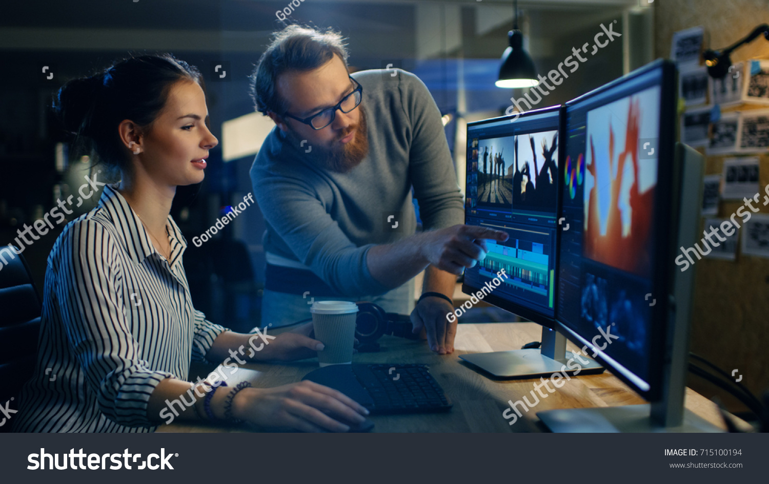 Female Video and Sound Editor Works With Her Male Colleague on a Project on Her Personal Computer with Two Displays. They Work in a Creative Loft Office. #715100194