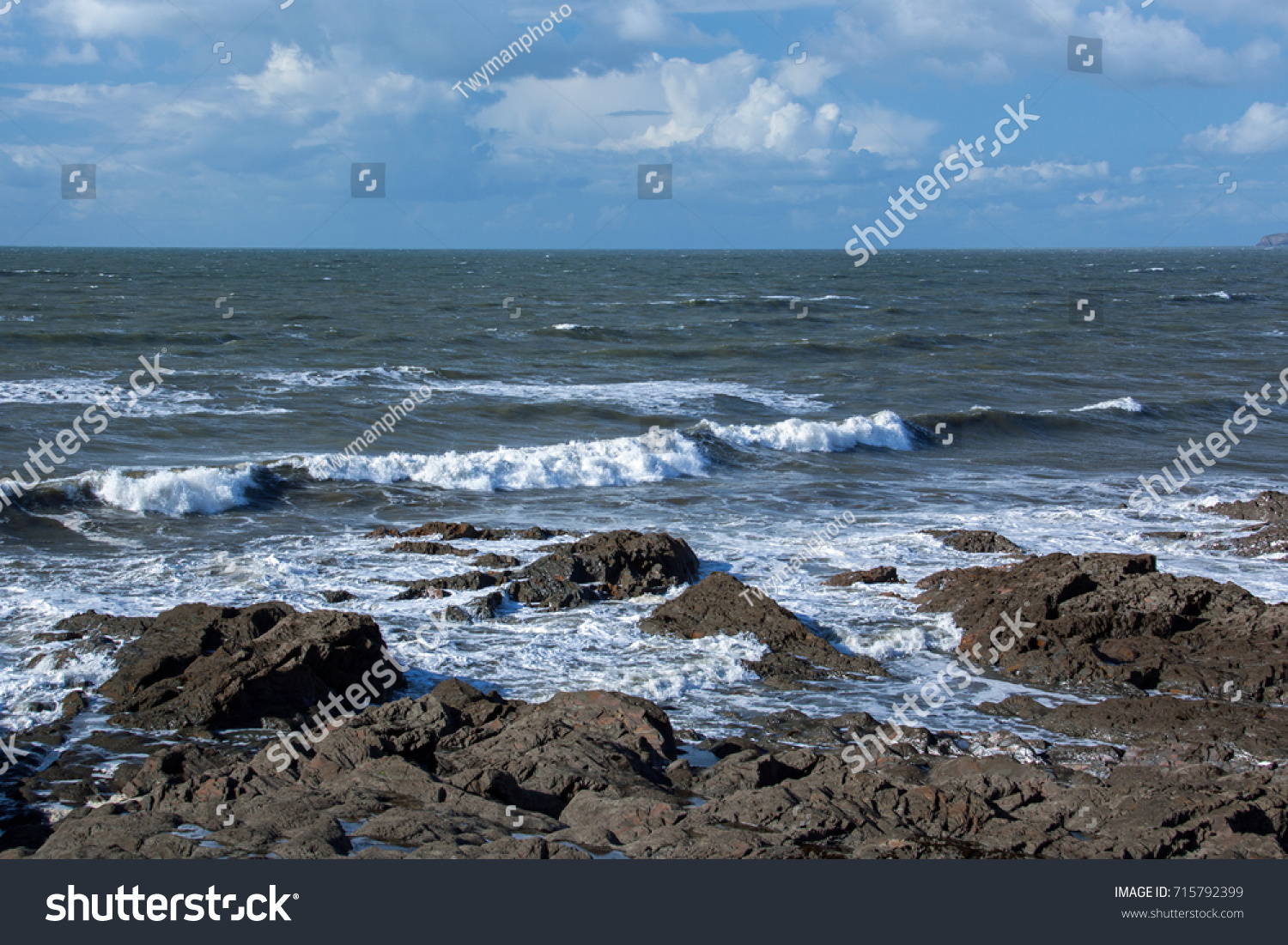 Waves crashing on the shoreline rocks #715792399