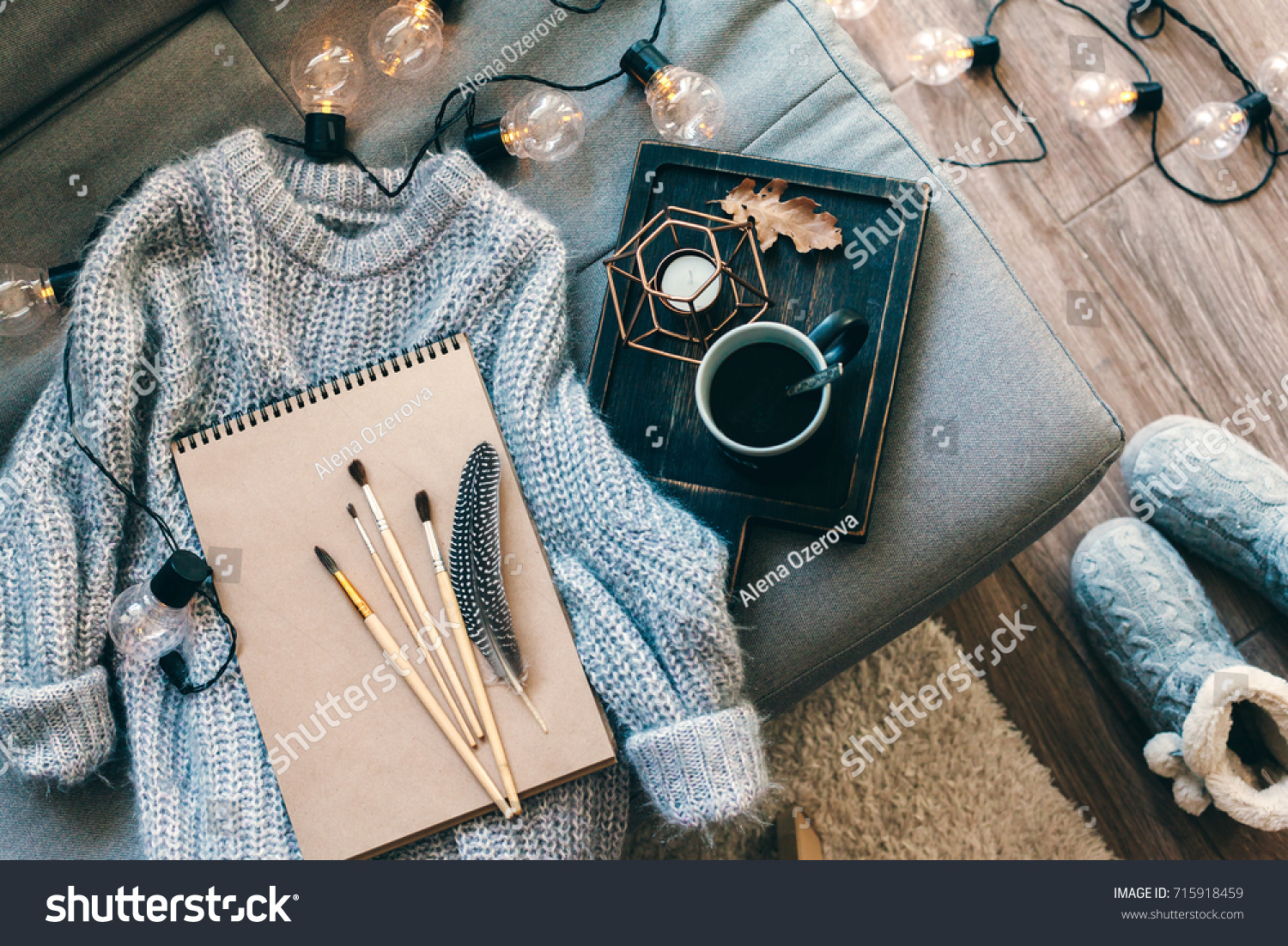 Still life details. Cup of coffee on rustic wooden tray, sketchbook and warm woolen sweater on sofa, decorated with led lights, top view point. Autumn weekend concept. Hobby and crafts. #715918459