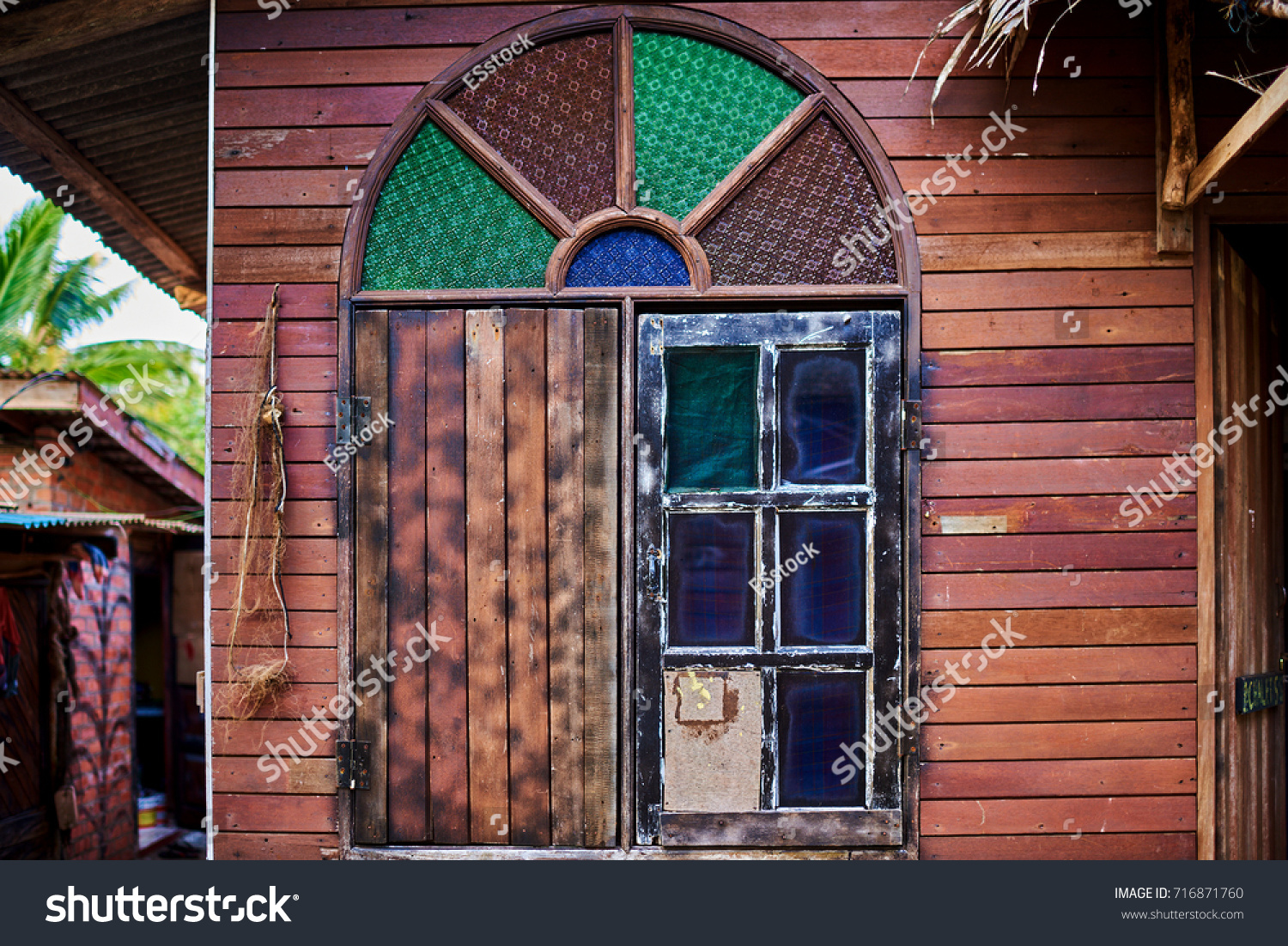 Old wooden window with color stained glass. Wooden window shutters pattern  on brown wall. Naked worn wooden and plain painted shutters.