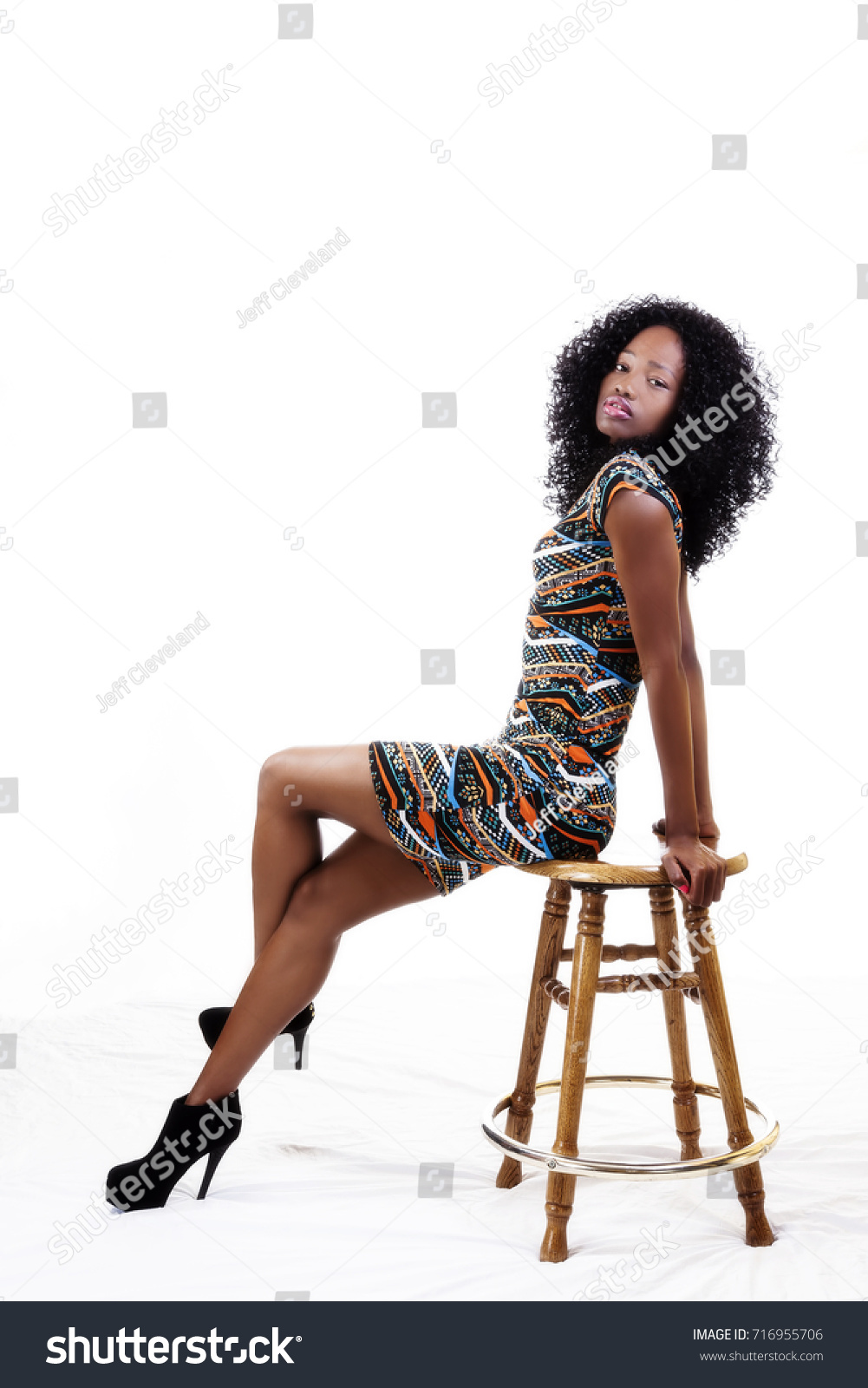 Attractive Slender African American Teen Girl Sitting On Edge Of Stool In Dress