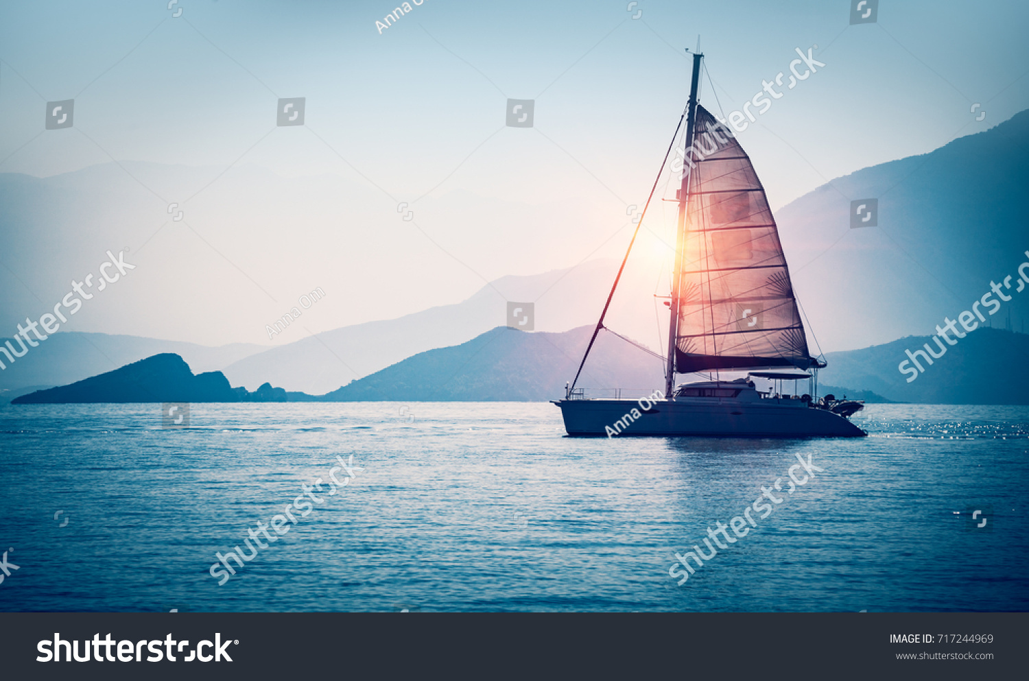 Sailboat in the sea in the evening sunlight over beautiful big mountains background, luxury summer adventure, active vacation in Mediterranean sea, Turkey #717244969