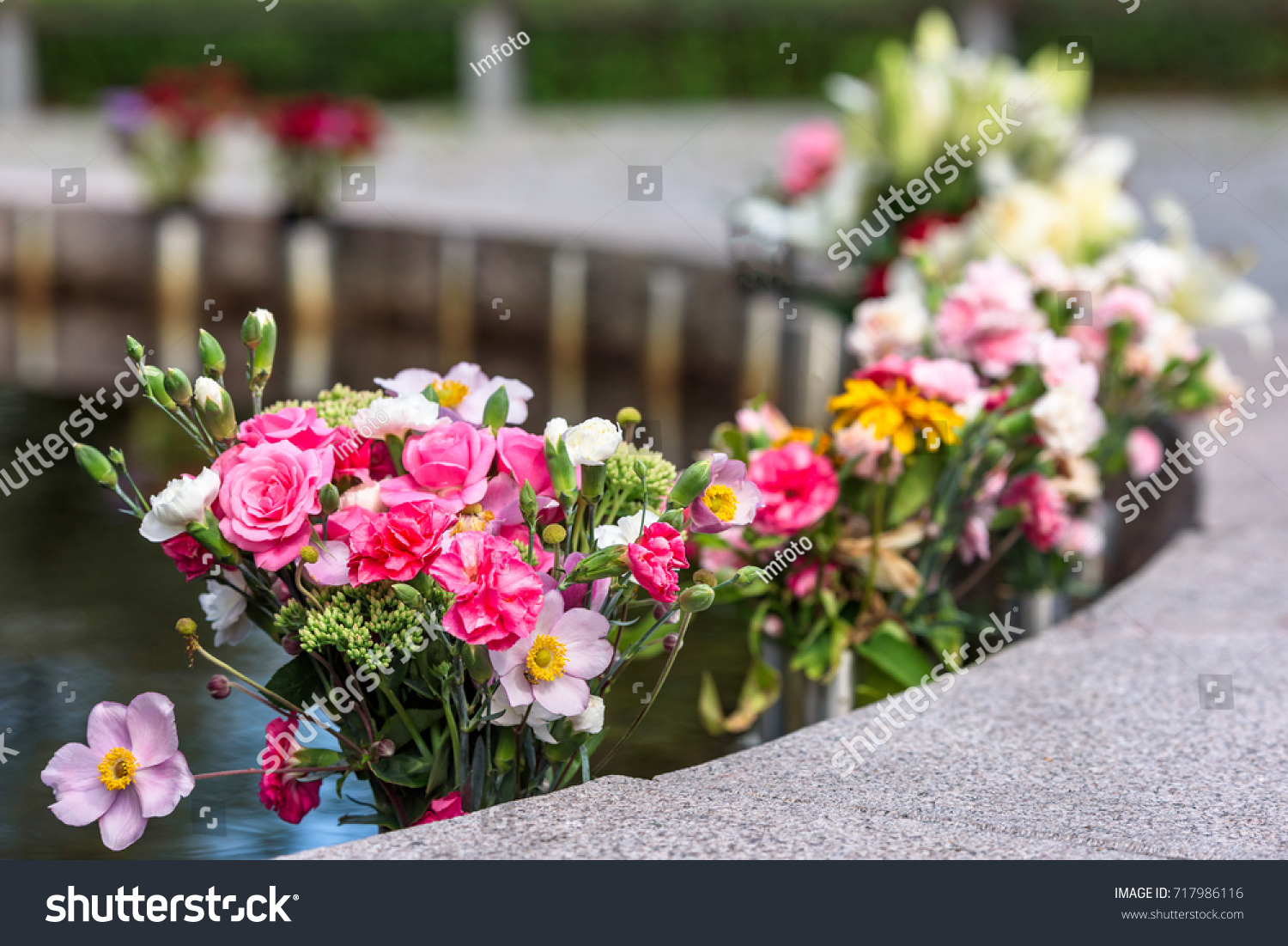 Flower Bouquets For The Dead Beside A Water Pond At A Memorial Site
