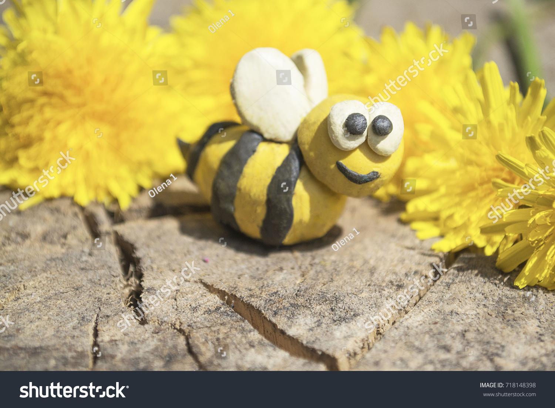 42a44dd46b Plasticine world . handmade bee on on wooden background.Dandelion flowers . handmade honeybee in