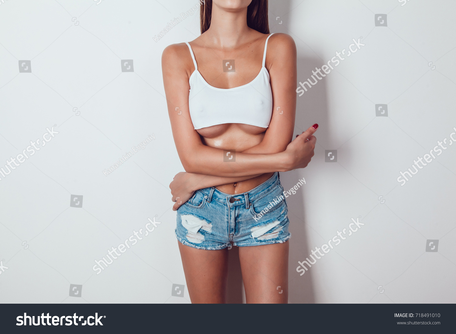 Body of a girl with big breasts with big breasts in a very short white tank