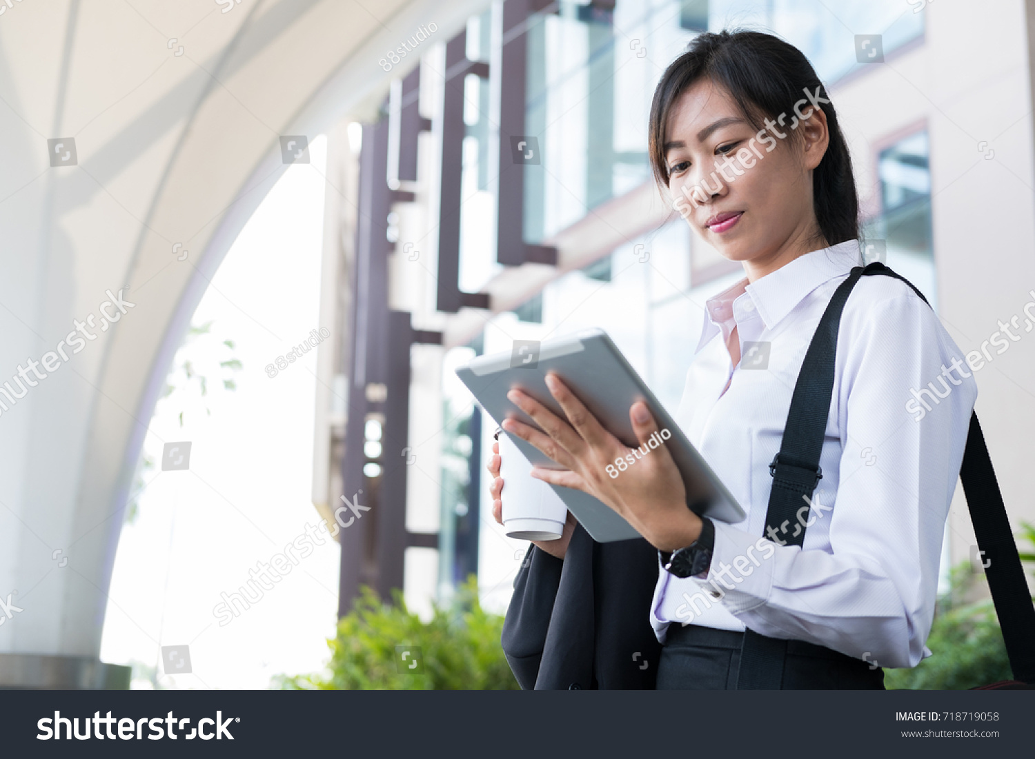 79f1cdd0bd businesswoman look at digital tablet outside office. happy young asian  woman with tea go to