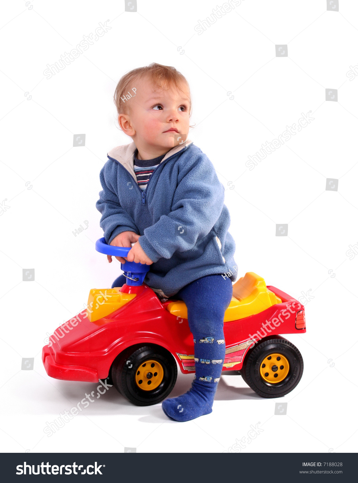 Little Boy With Toy Car : Little blond boy driving a red toy car stock photo