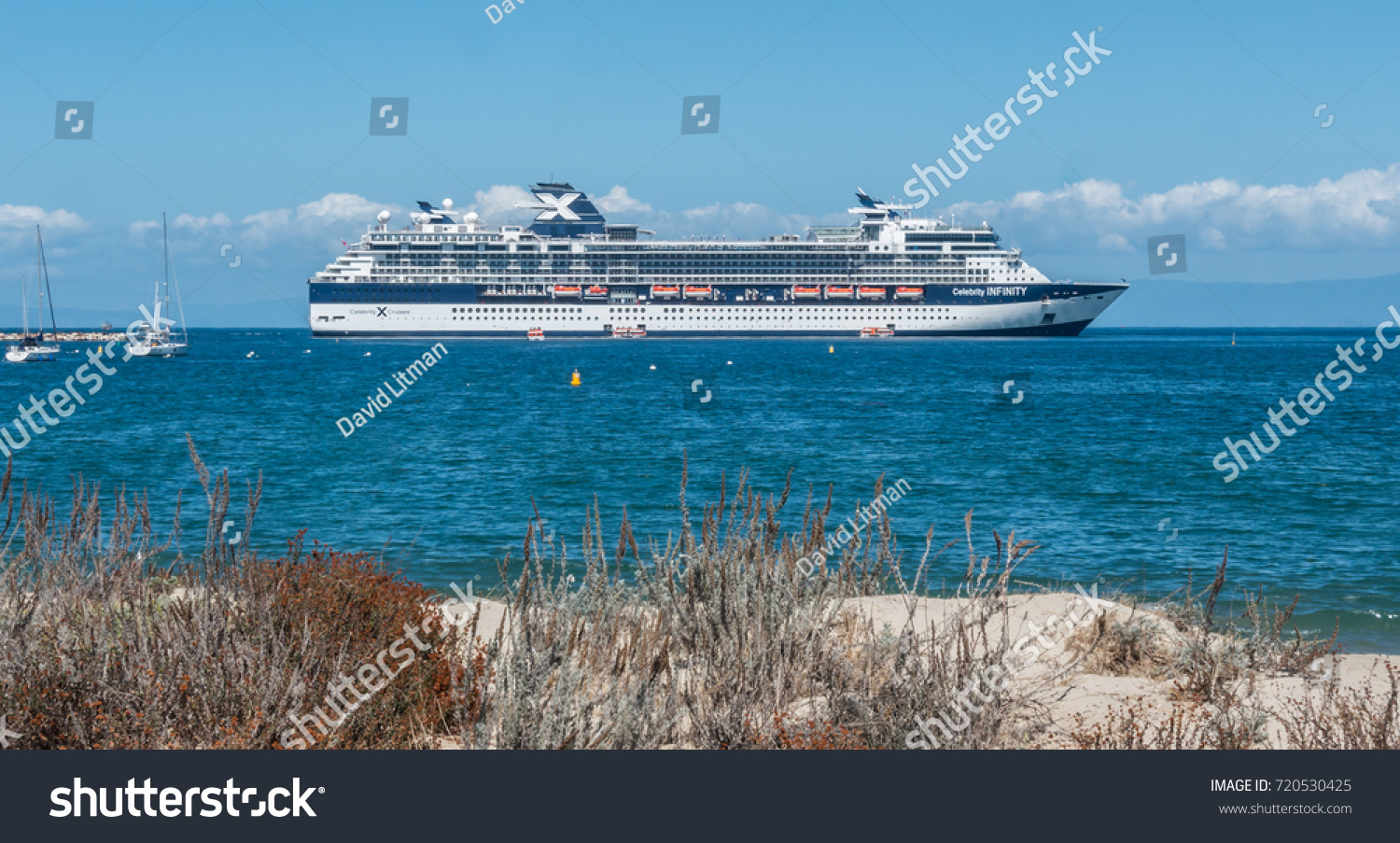 Monterey, California - September 22, 2017: The cruise ship Celebrity Infinity, anchored in the Monterey Bay, is viewed from the coastal sand dunes nearby.  It can hold up to 2200 people.