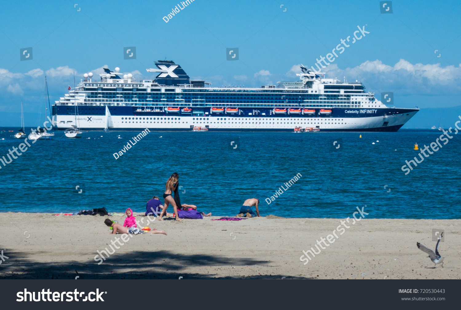 Monterey, California - September 22, 2017: The cruise ship Celebrity Infinity is anchored in the Monterey Bay as people enjoy a sunny day at Del Monte Beach.