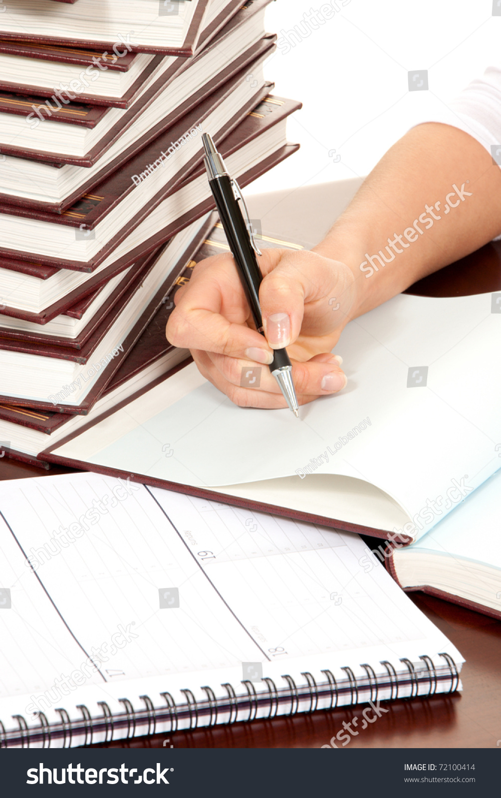 Writer business person hand with pen signing document. On the table stack  of books organizer