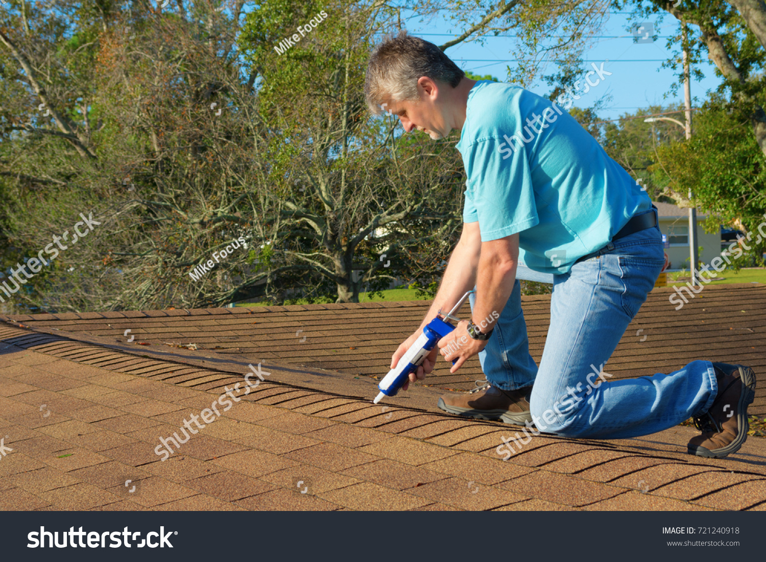 Homeowner Patching Roof With Roof Repair Tar In Caulk Gun Doing Home  Maintenance To Protect And