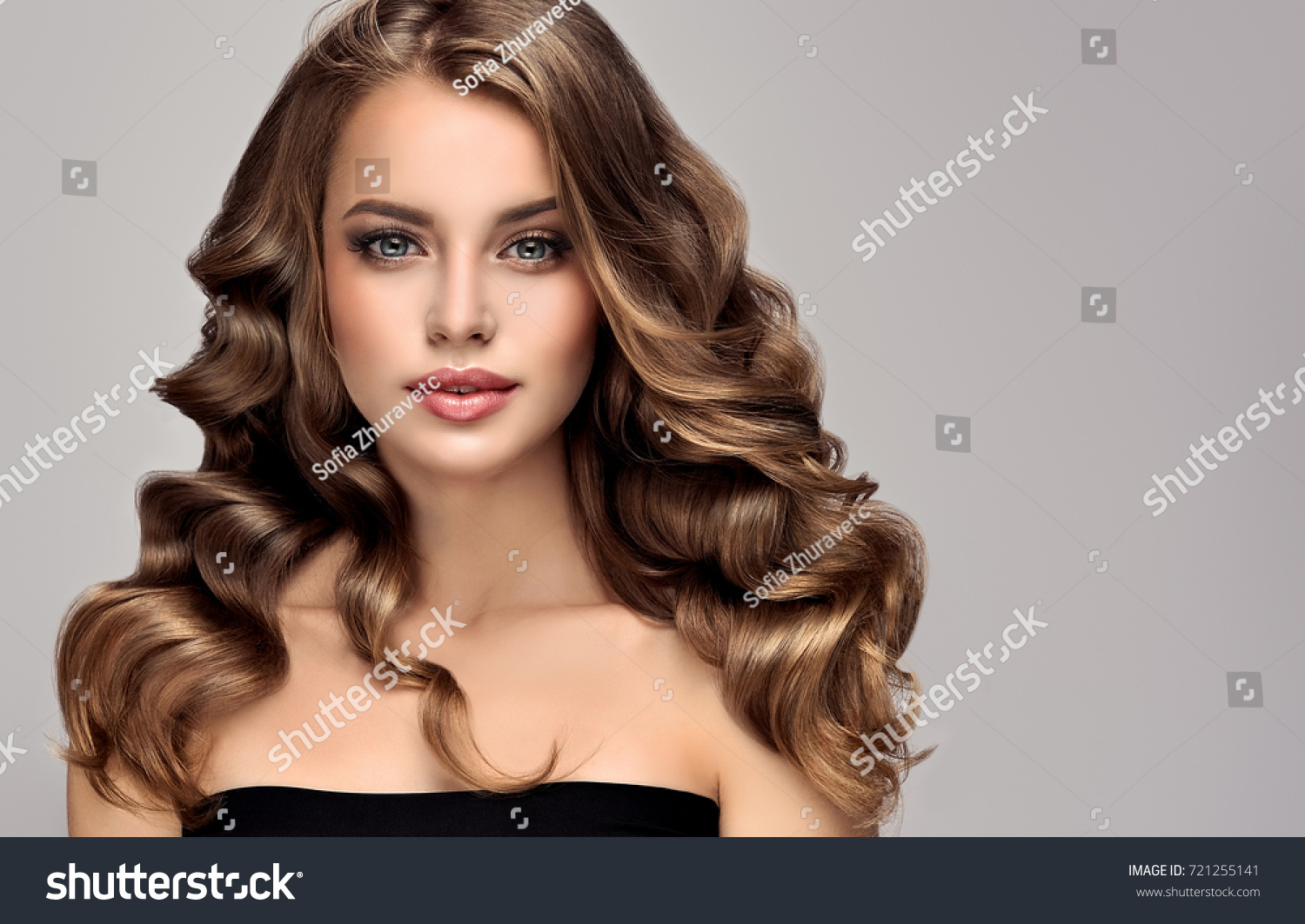Brunette  girl with long  and   shiny curly hair .  Beautiful  model woman  with curly hairstyle   .Care and beauty of hair #721255141