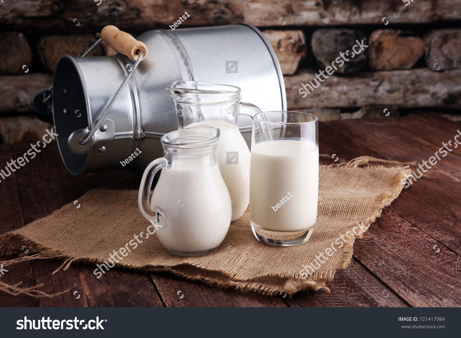 A jug of milk and glass of milk on a wooden table #721417984
