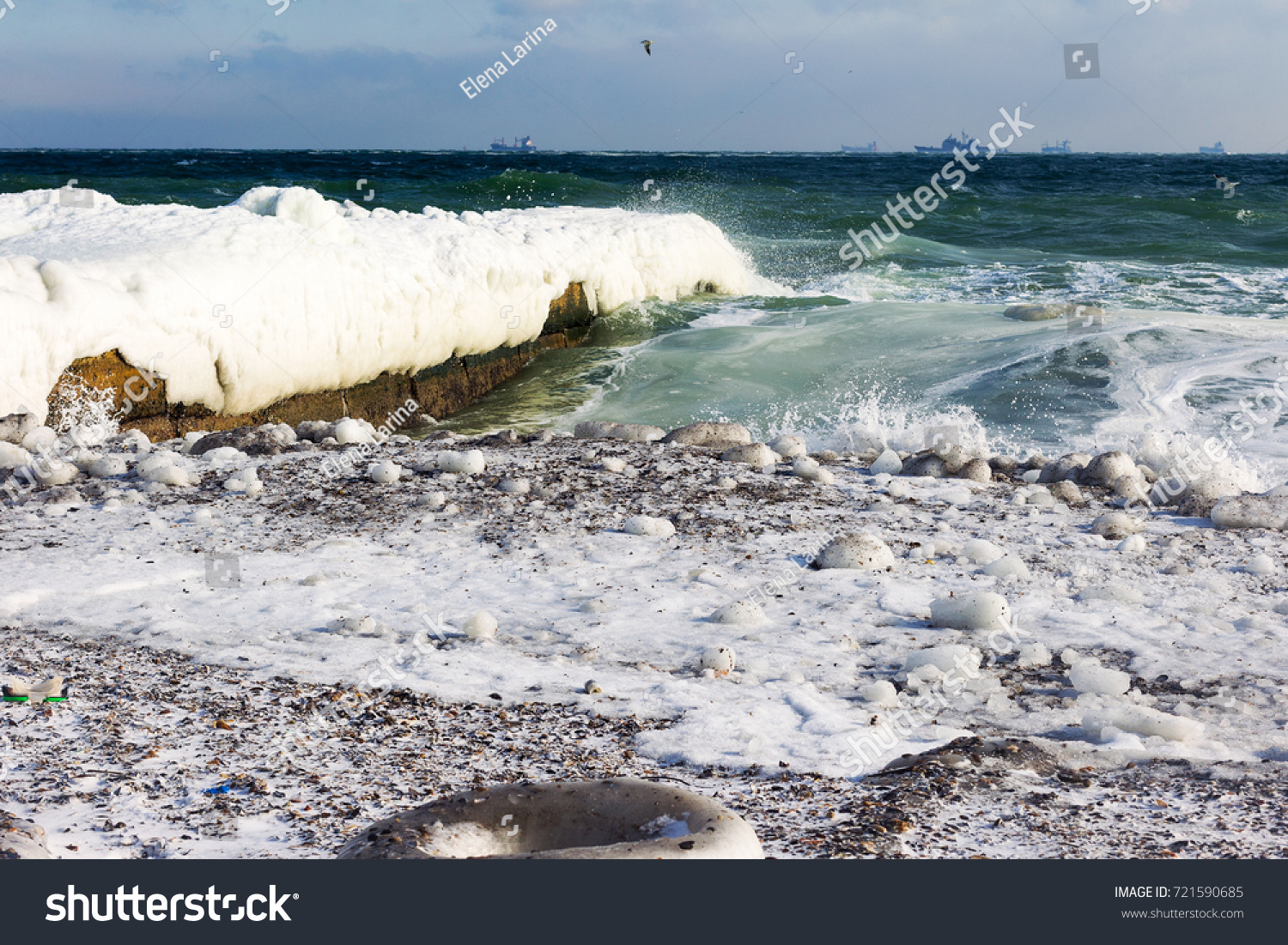 Winter seascape. Snow, ice huge waves beating against the shore and freezes. Natural disaster in form of storms and severe frosts led to icing of the black sea coast near Odessa.  #721590685