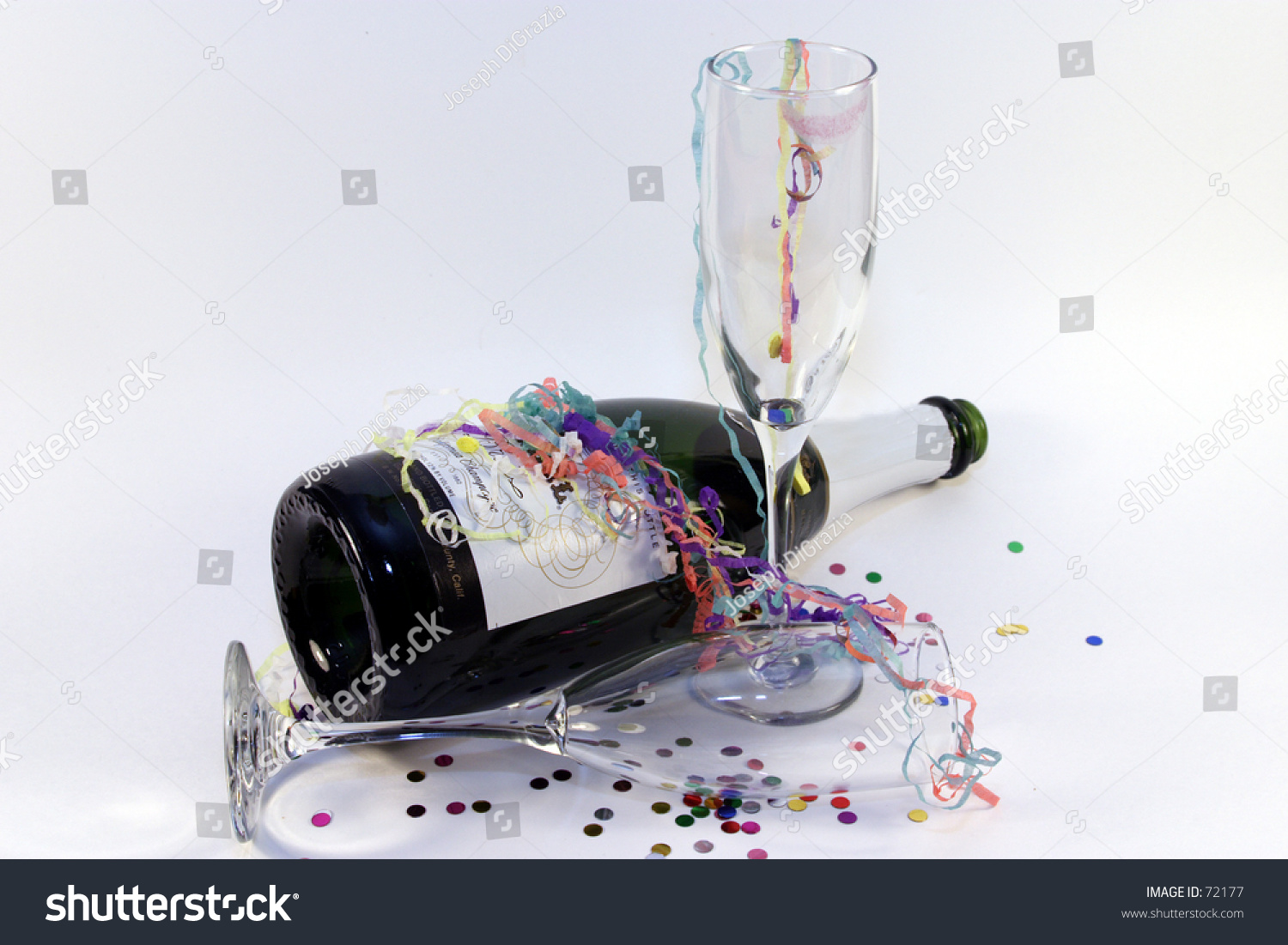 Empty Champagne Bottle With Used Glasses, Confetti, And Streamers