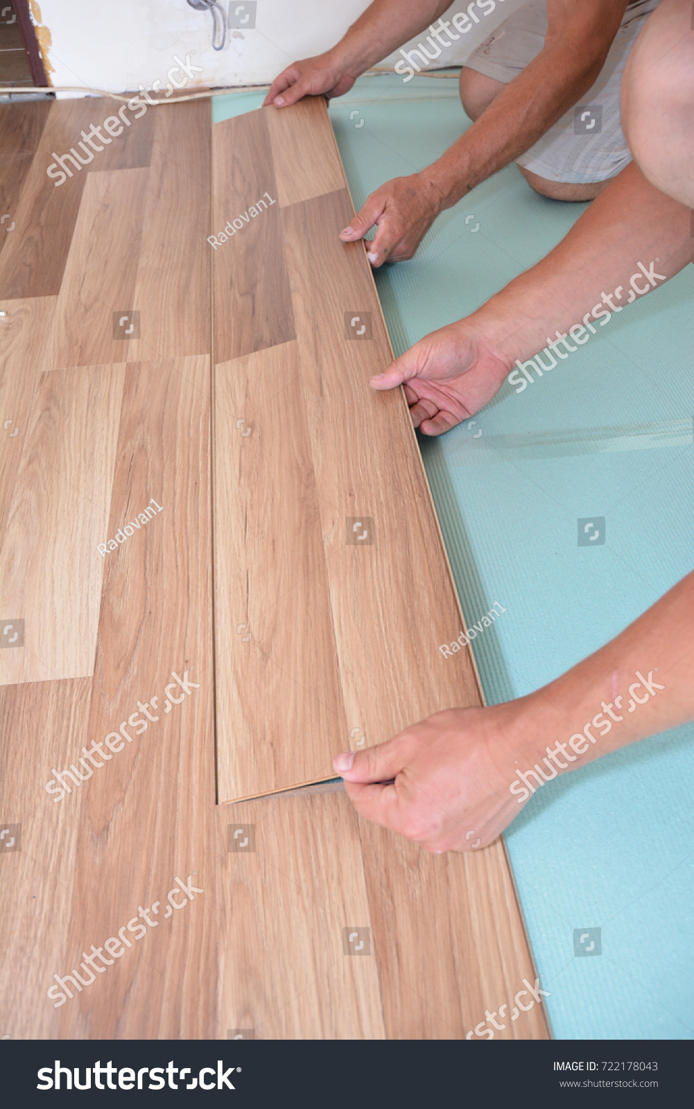 Contractors Installing Wooden Laminate Flooring With Insulation And Soundproofing Sheets Man Laying