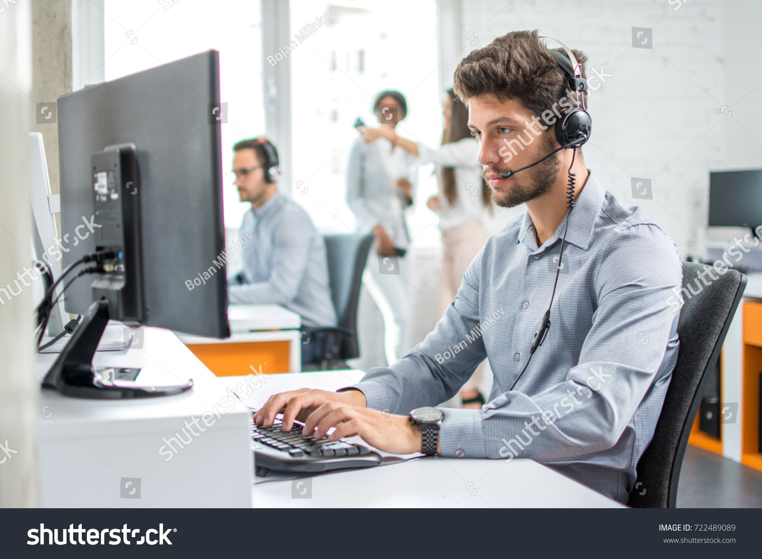 Young handsome male customer support phone operator with headset working in call center. #722489089