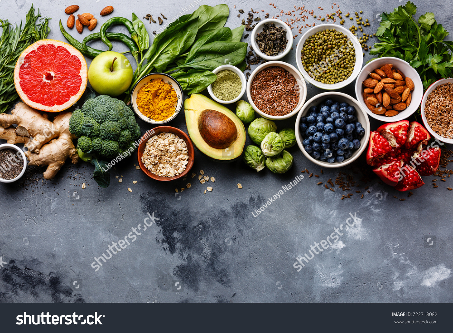 Healthy food clean eating selection: fruit, vegetable, seeds, superfood, cereals, leaf vegetable on gray concrete background copy space #722718082