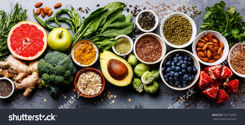 Healthy food clean eating selection: fruit, vegetable, seeds, superfood, cereal, leaf vegetable on gray concrete background #722718097