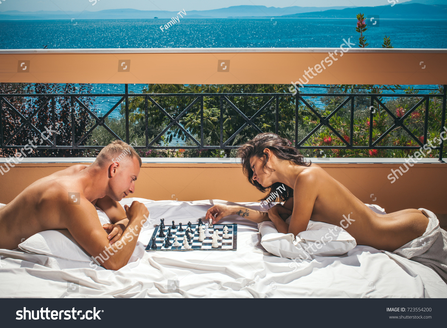 Sexy couple. Young couple playing chess indoor, woman moving with knight.  Passionate couple