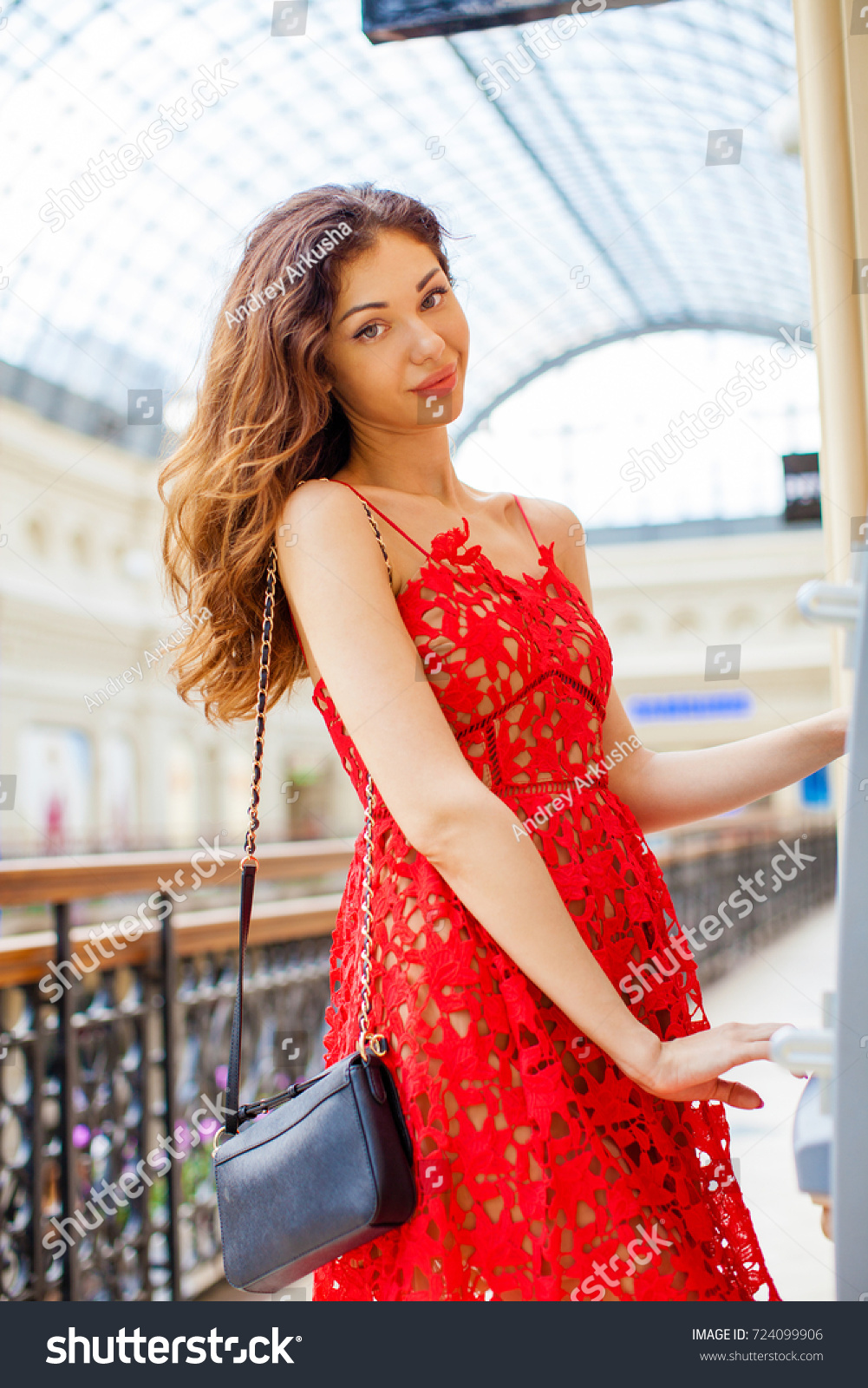 87046292f7de Young happy blonde woman in red dress withdrawing money from credit card at  ATM