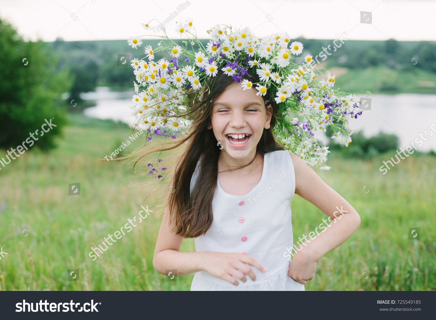 Little laughing girl wear wreath on her head look on the sky  #725549185